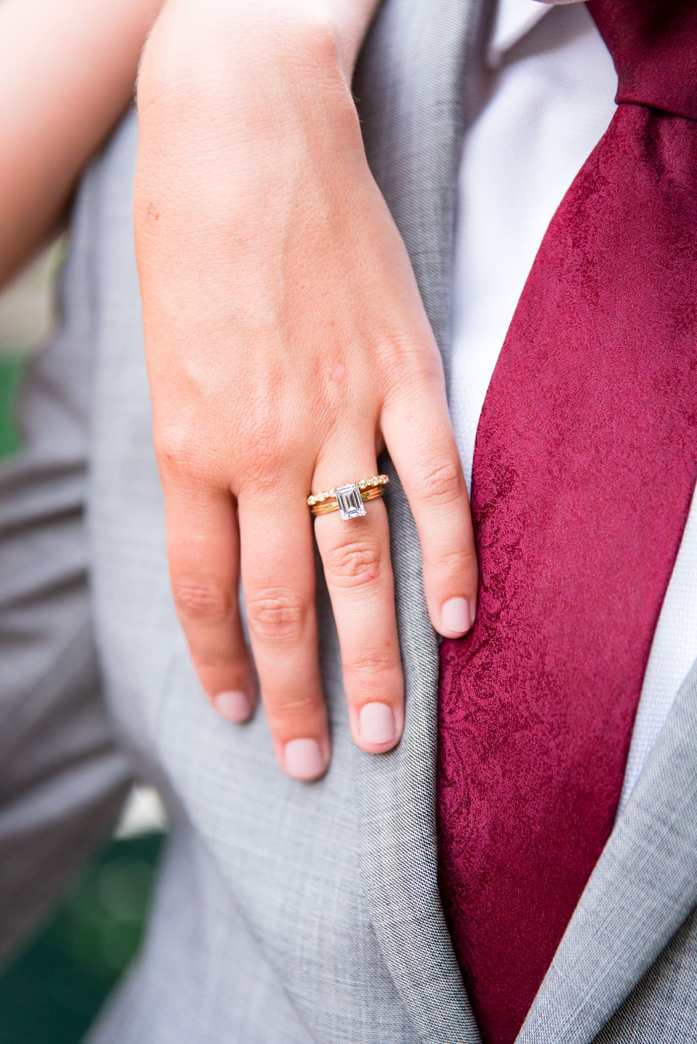bride resting hand on grooms chest, showing her emerald cut engagement ring and his gray suit and red tie