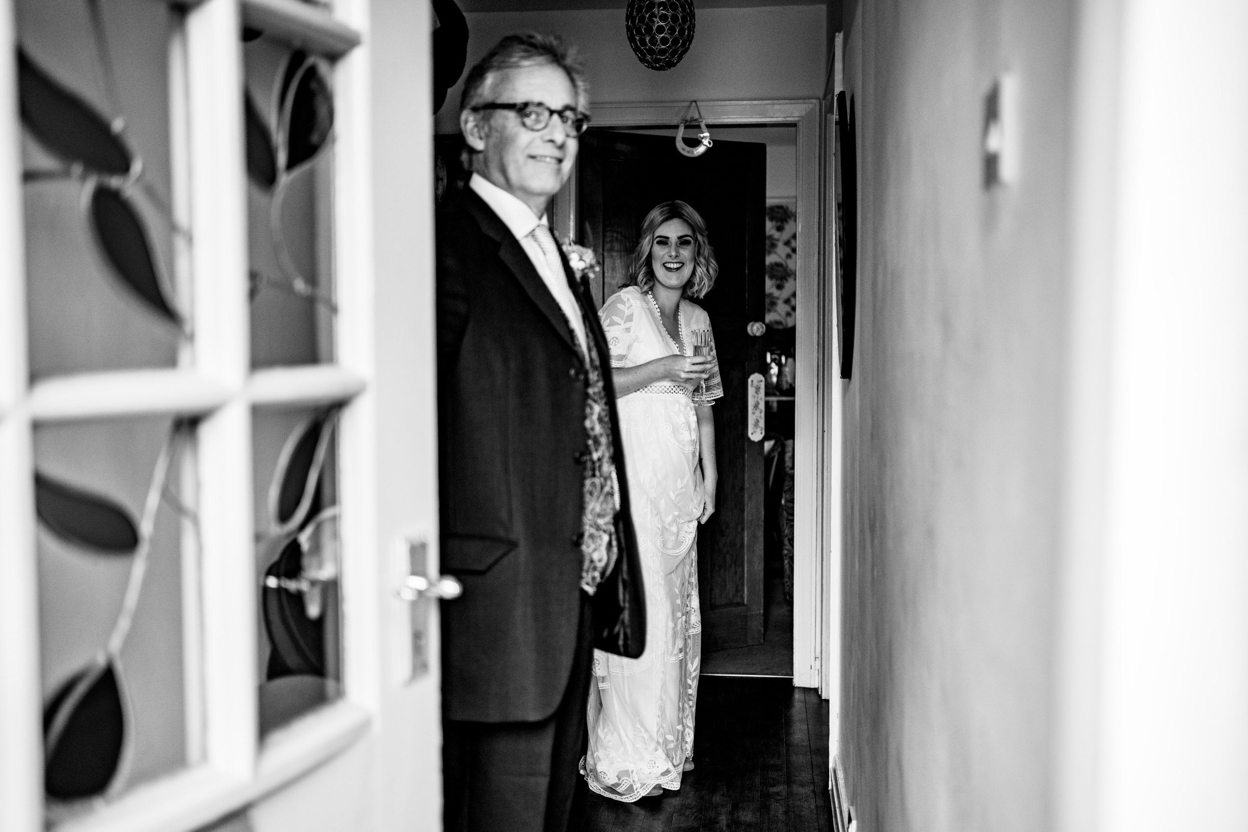 father of bride and bride waiting at the door