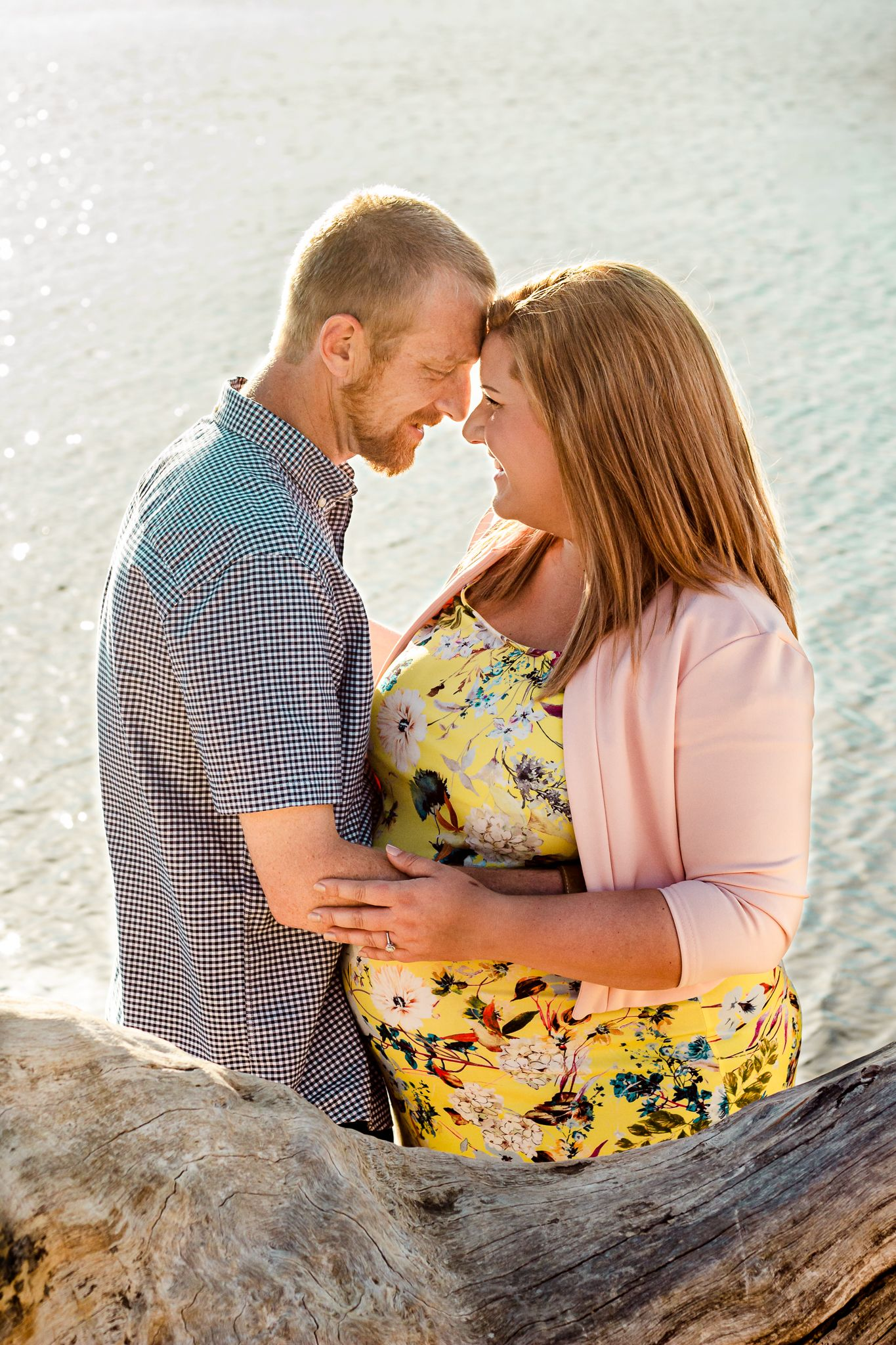 A maternity couple embrace and smile at each other by the sea on a Hayling Island Beach while the sun sets behind them.