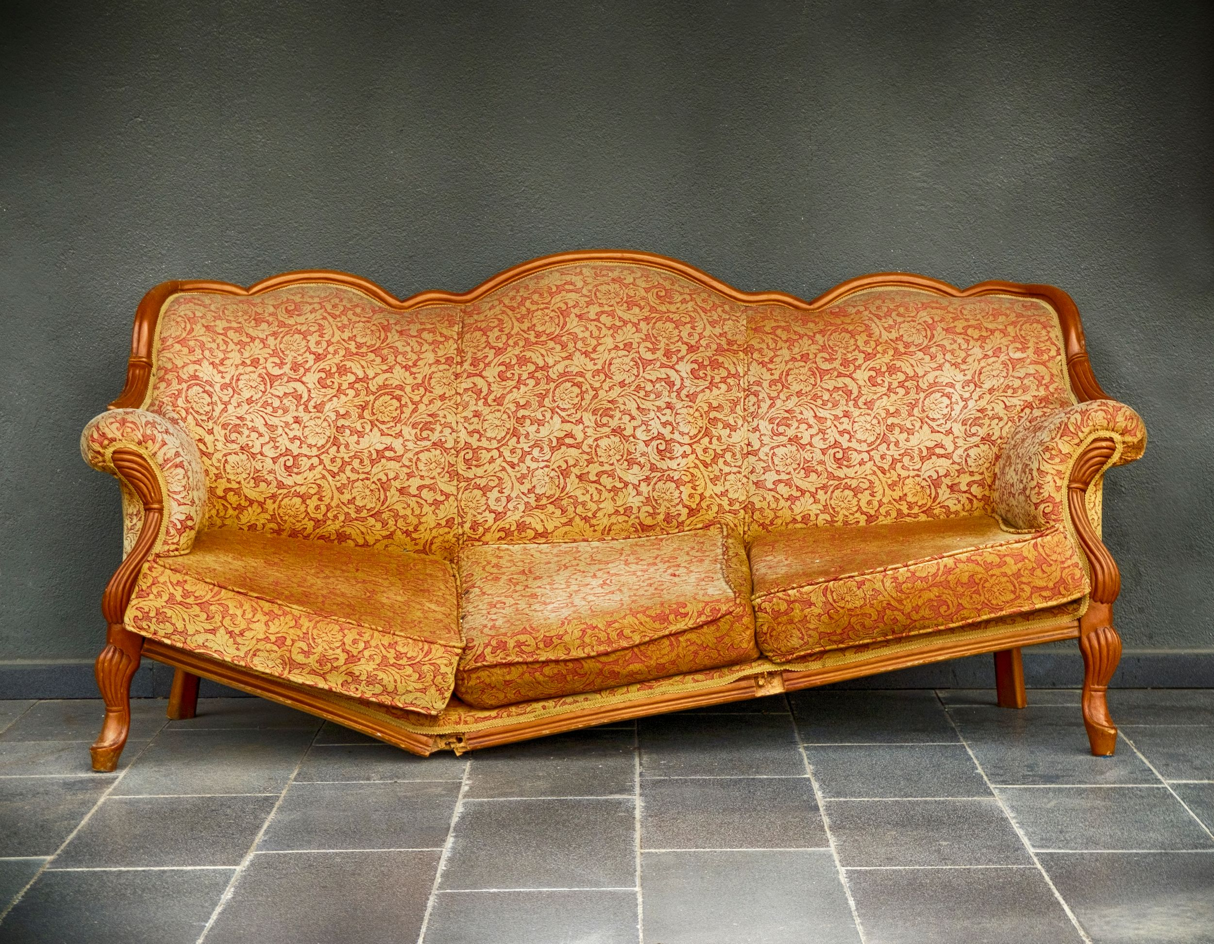 Broken orange couch - purchase a furniture protection plan