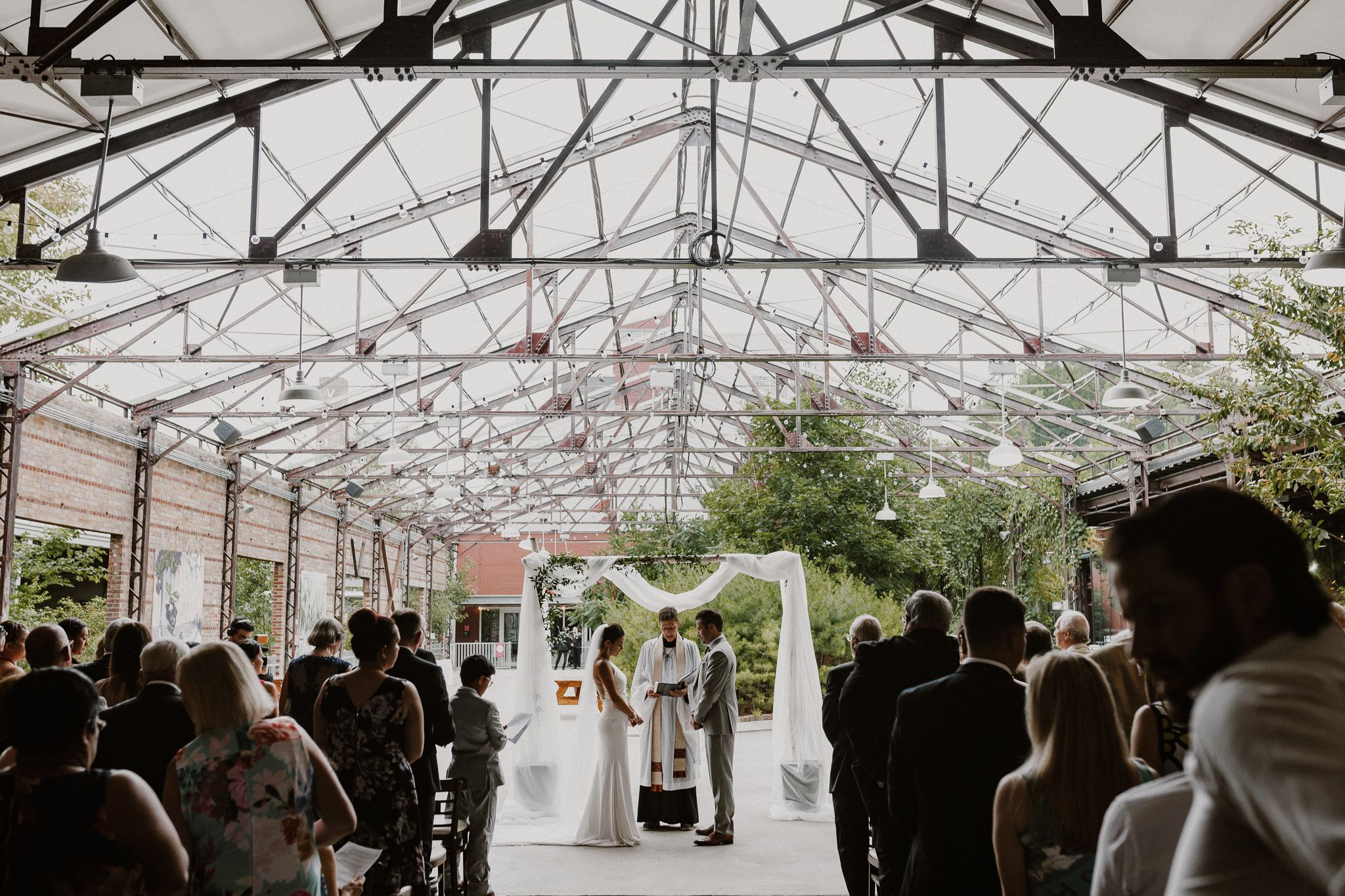 Bride and groom ceremony photo at Evergreen Brick Works looking at each other with priest and guests present.