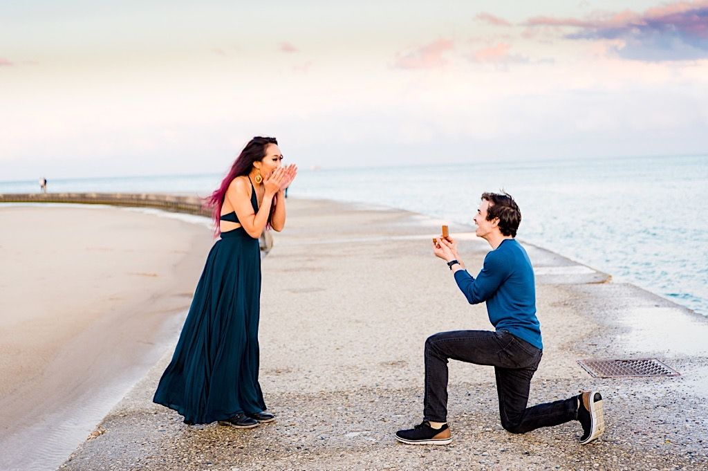 woman in teal dress covering mouth with hands since she's shocked her boyfriend is proposing