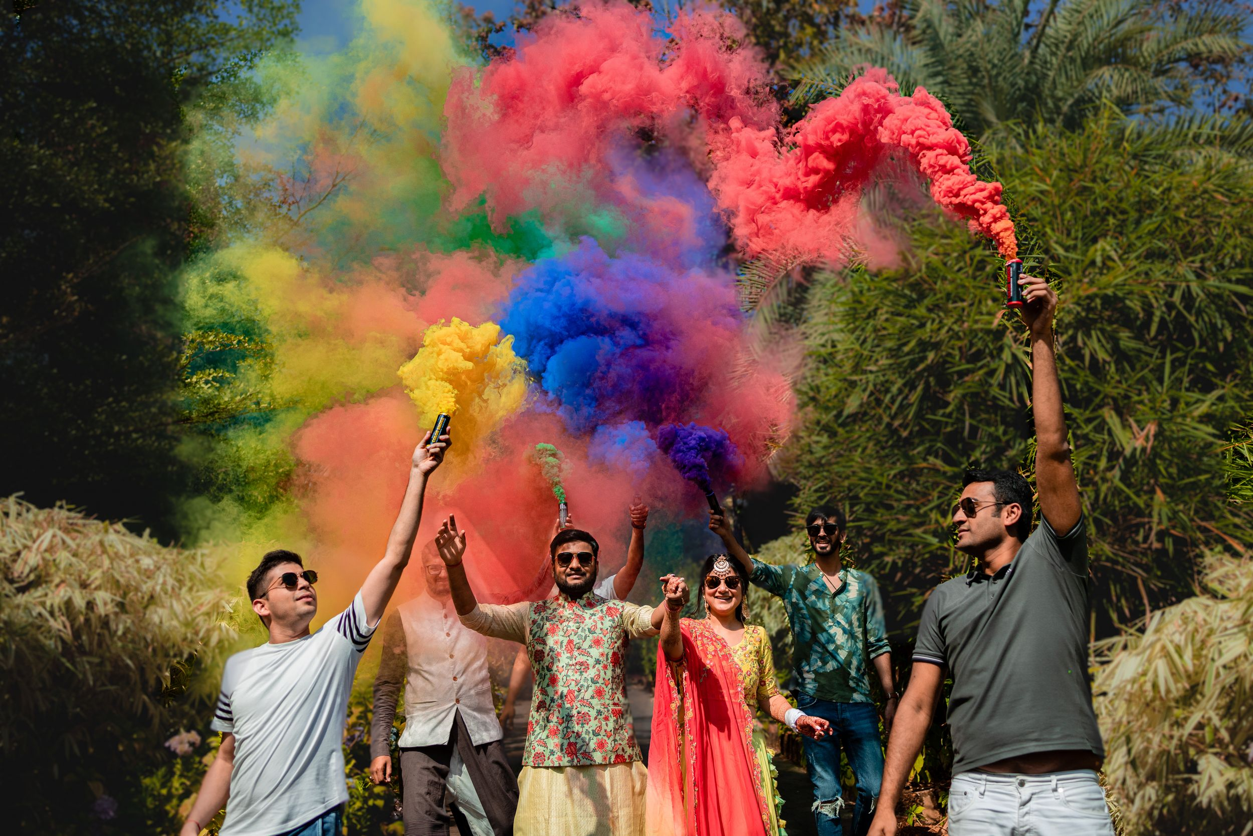 wedding day couple entry with  friends holding color smoke bombs at goa