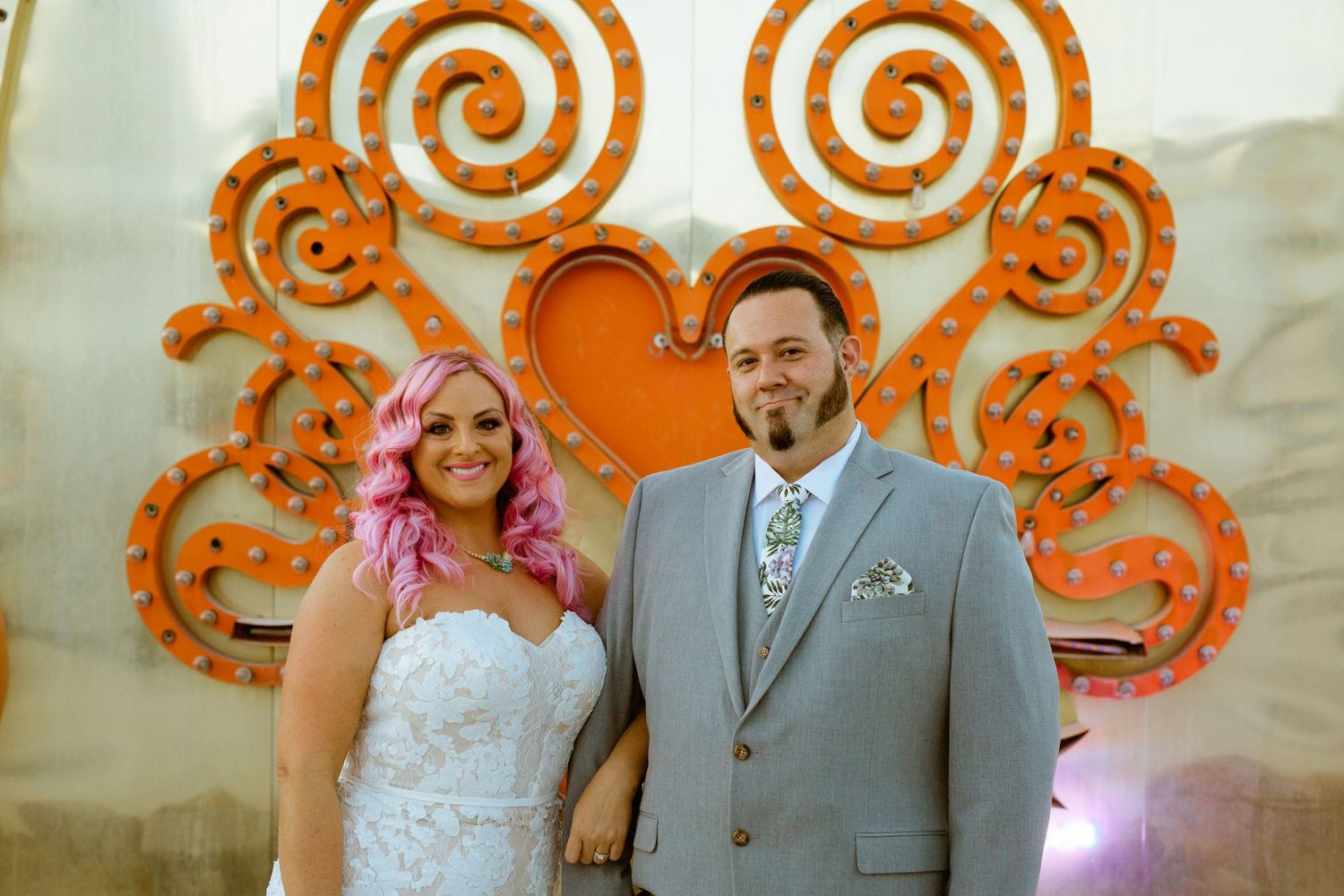 couples shot in front of neon sign at the neon museum
