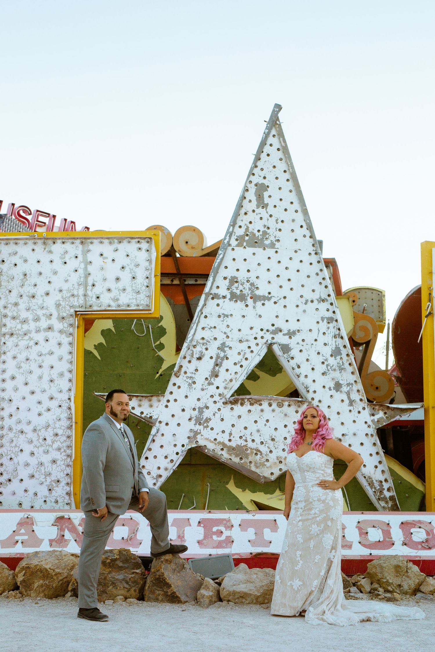 couples pose in front of neon sign at the neon museum