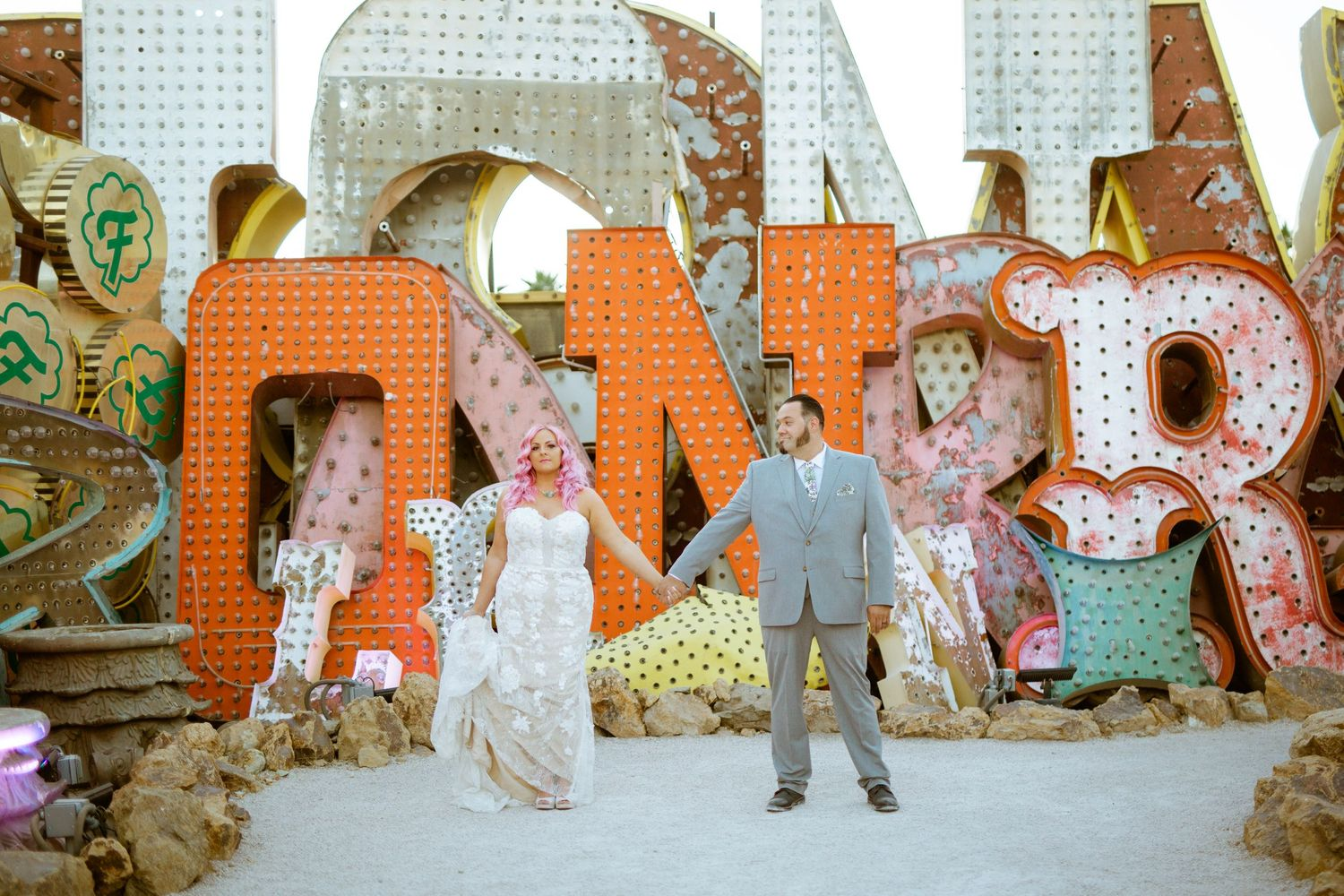 whimsical couples in front of neon sign at the neon museum
