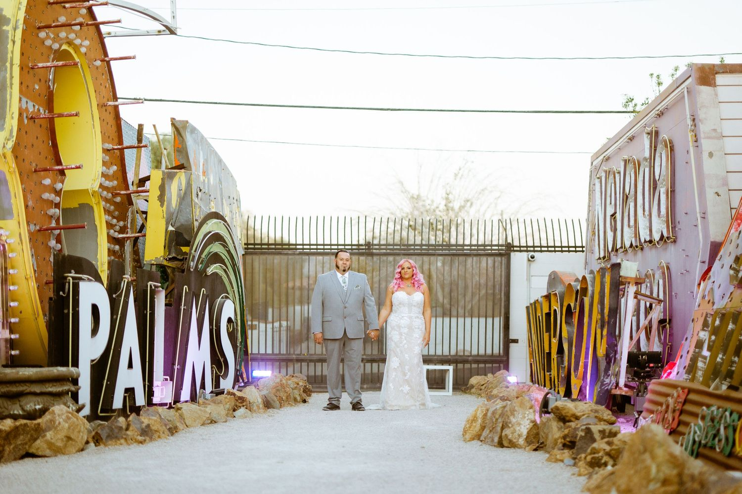 whimsical couples casually pose in front of neon sign at the neon museum