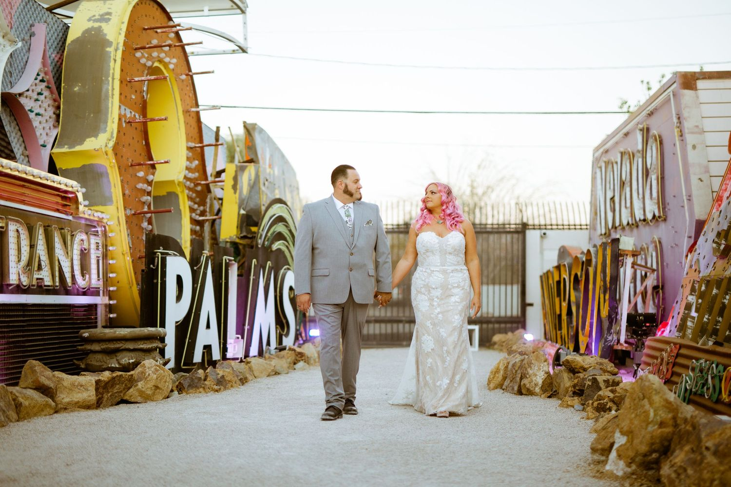 couples casually pose in front of retired neon sign at the neon museum