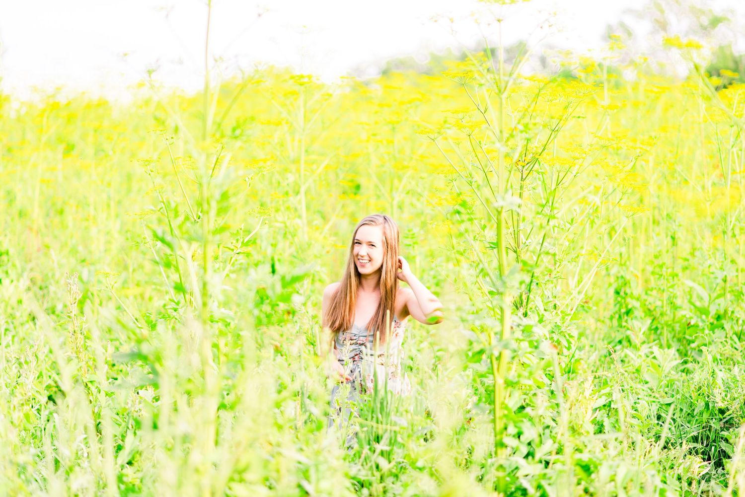 young woman standing in field of giant yellow flowers for summer senior pictures at Montrose Bird Sanctuary in Chicago