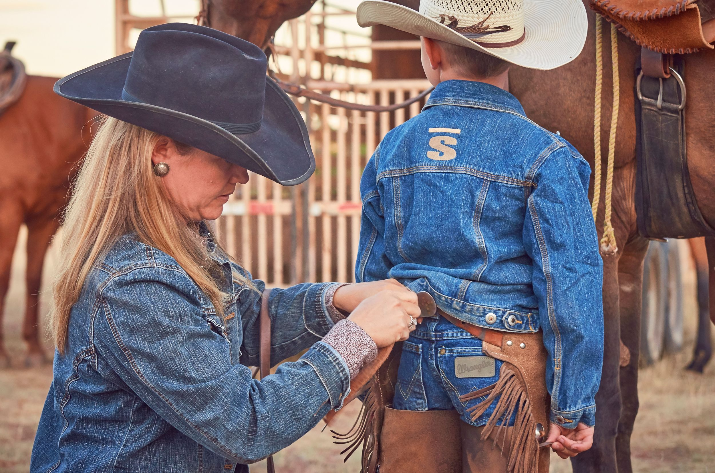 Mother helping young cowboy buckle his chaps