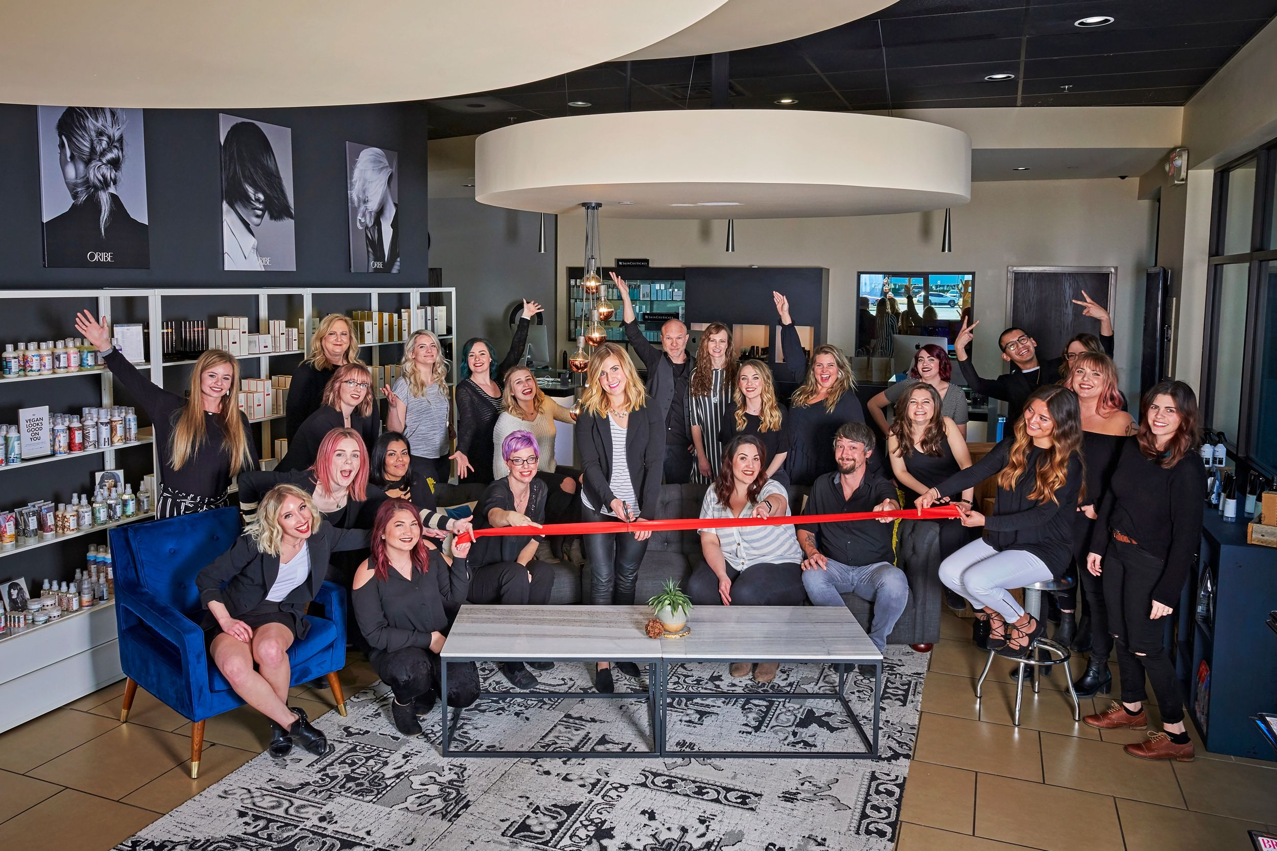 Employees at hair salon cutting ribbon for new business