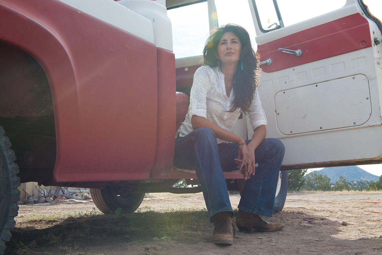 Brunette woman sitting in old red and white truck