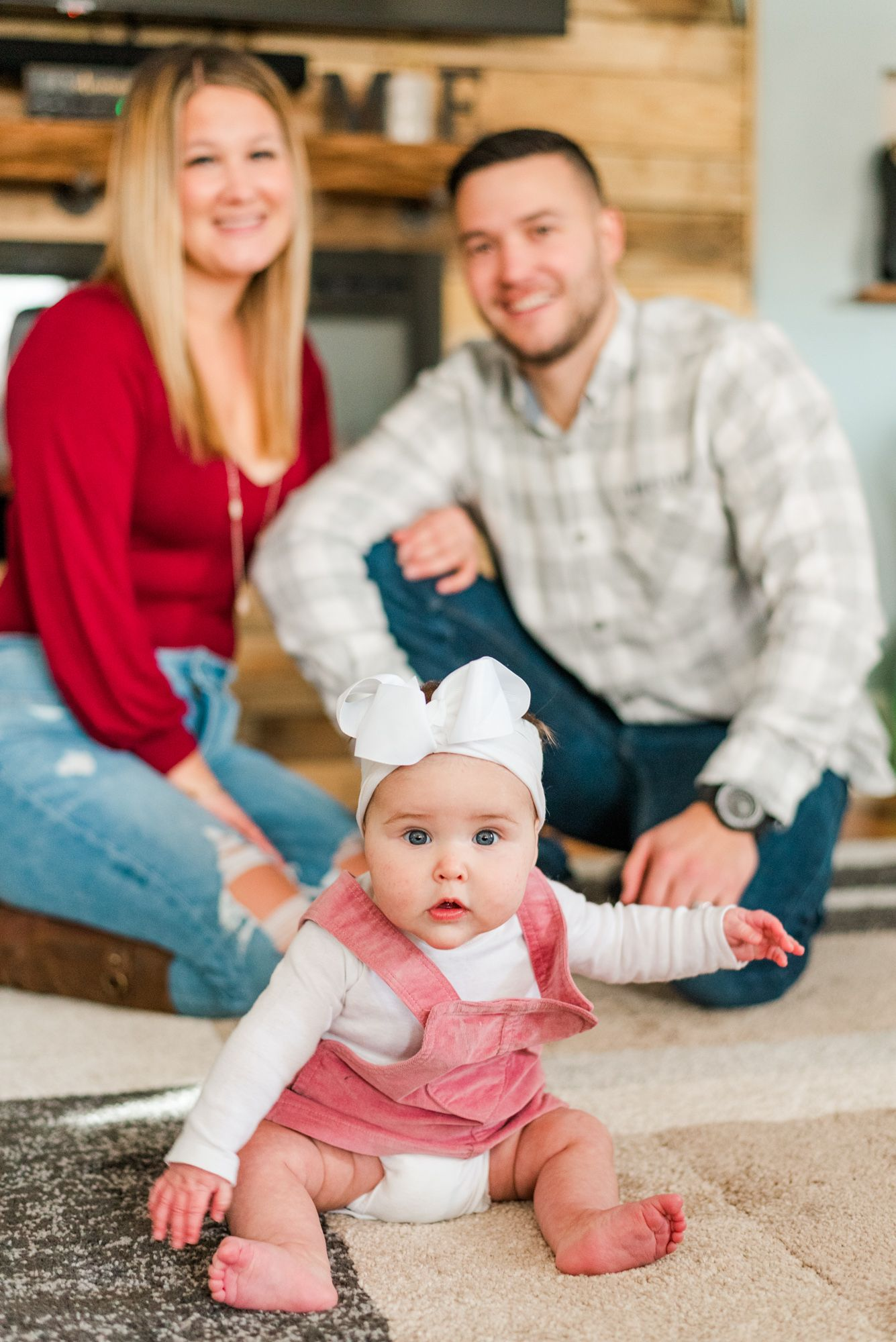 Lifestyle family photoshoot in the home with mom and dad and 6 month old baby wearing bow in Gibsonia, Pennsylvania