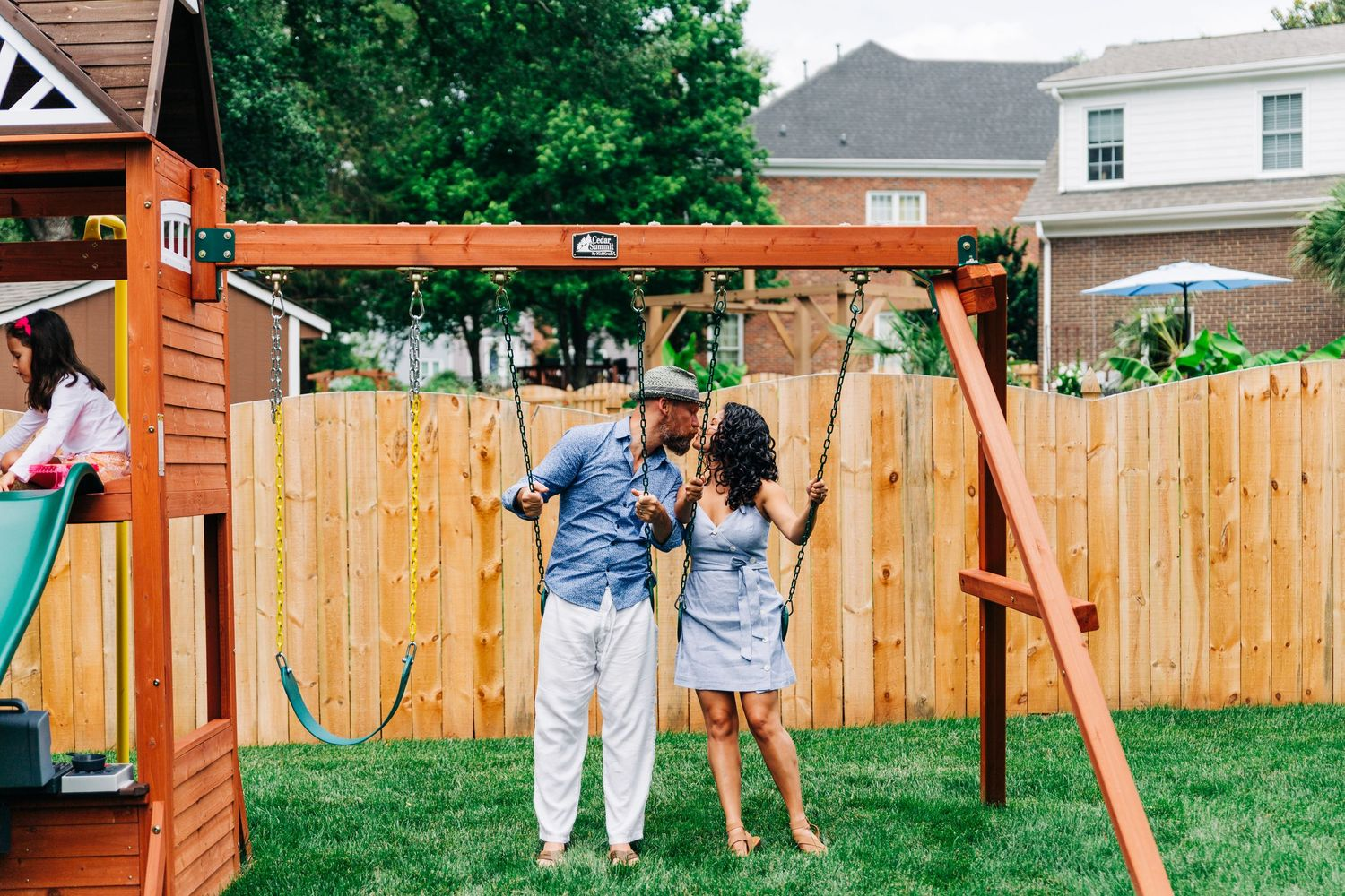 Parents kissing on swing set during Charlotte family photos