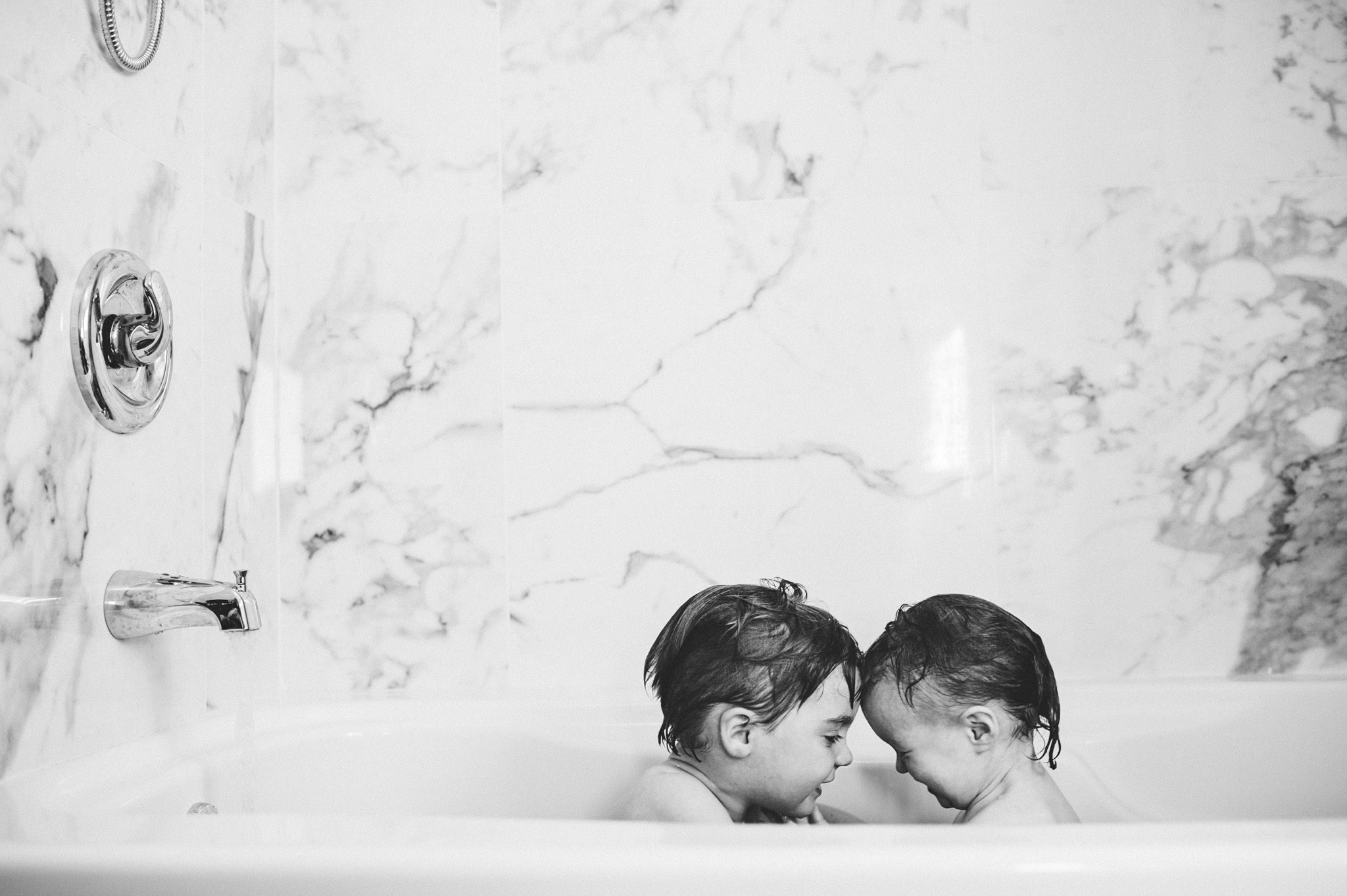 Black and white image of brother and sister in bath.