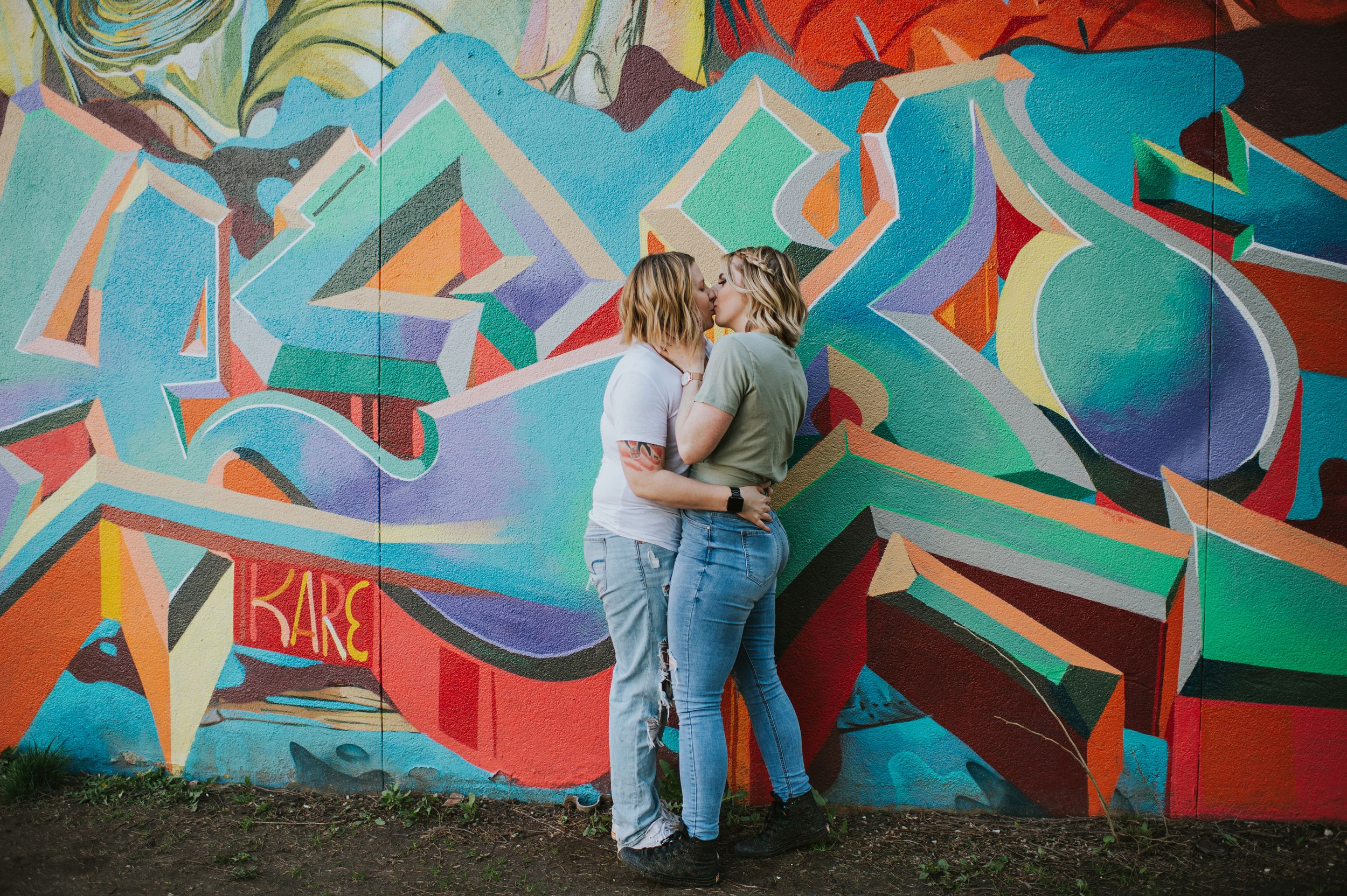 Two women embrace in a passionate kiss in front of a graffiti wall.