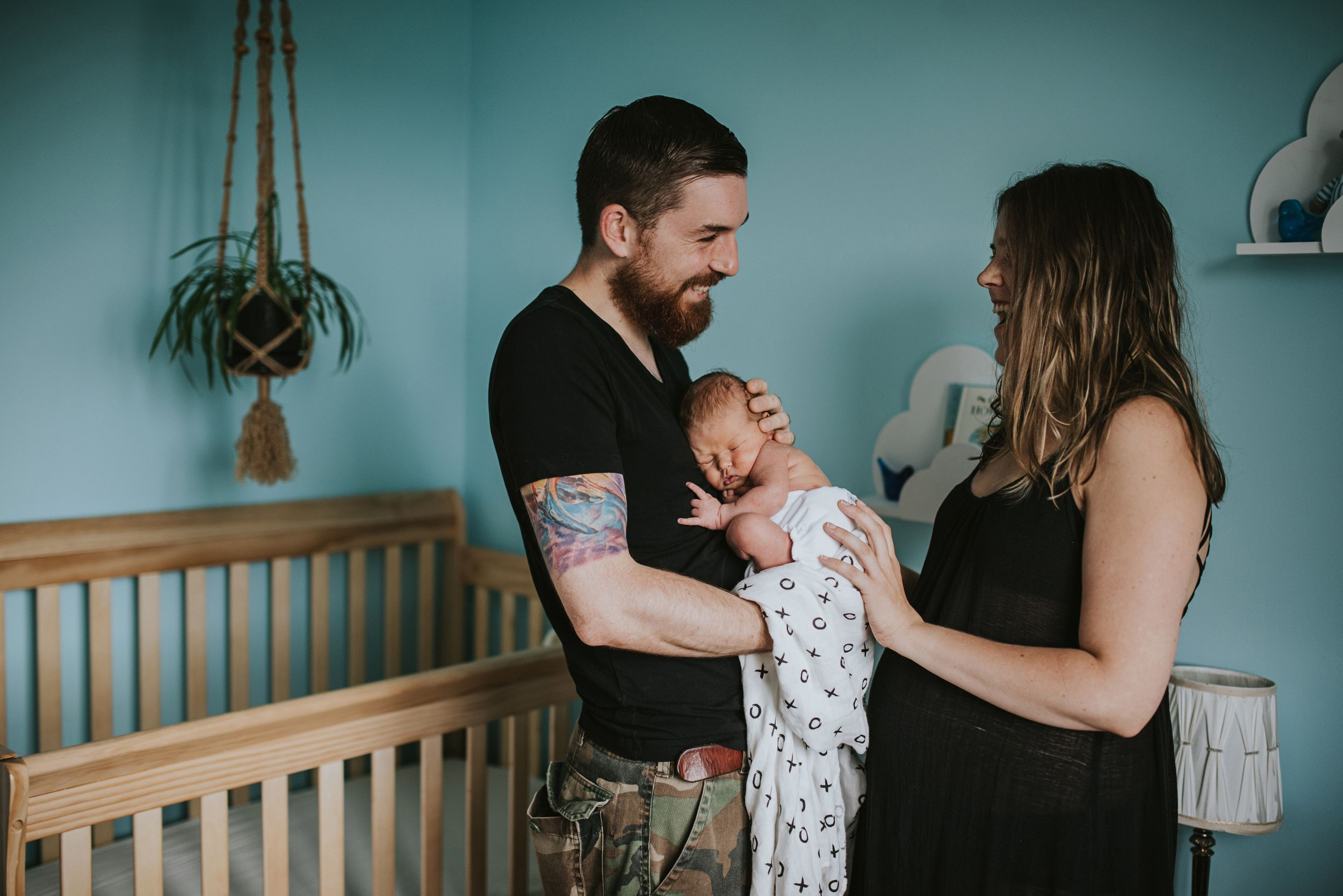 Tattooed father holds newborn son with his wife, the child is giving metal hand sign for rock on.