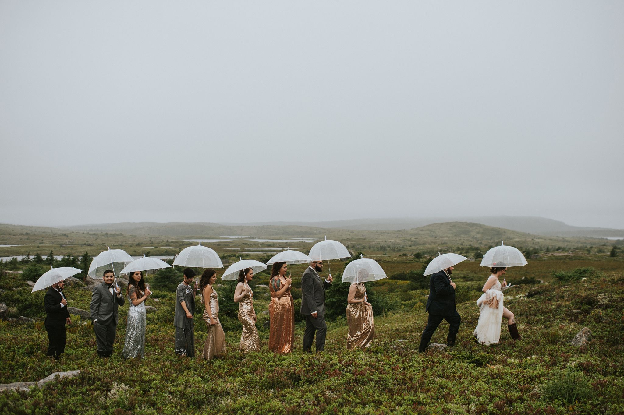 A brightly dressed bridal party walk across a barren marsh in a straight line holding umbrellas.