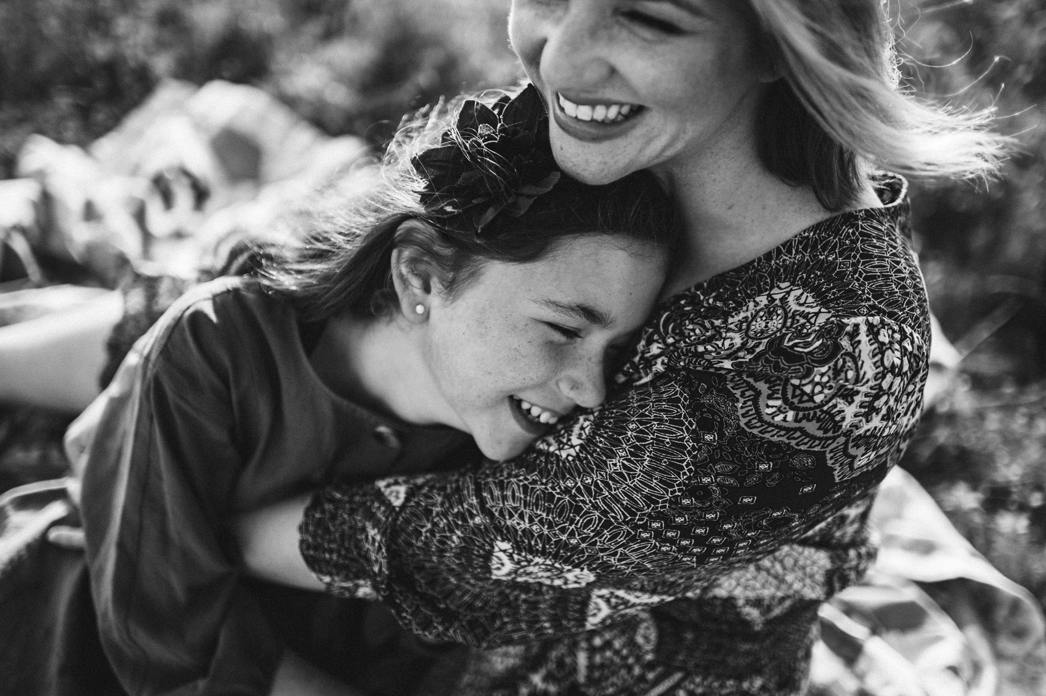 Mother and daughter hugging and laughing black and white