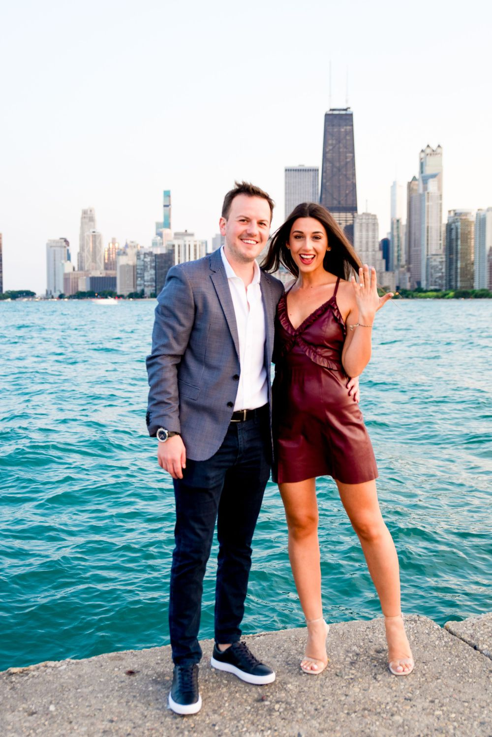 woman in maroon leather dress holding up her hand showing she is engaged in front of Chicago skyline at North Ave Beach