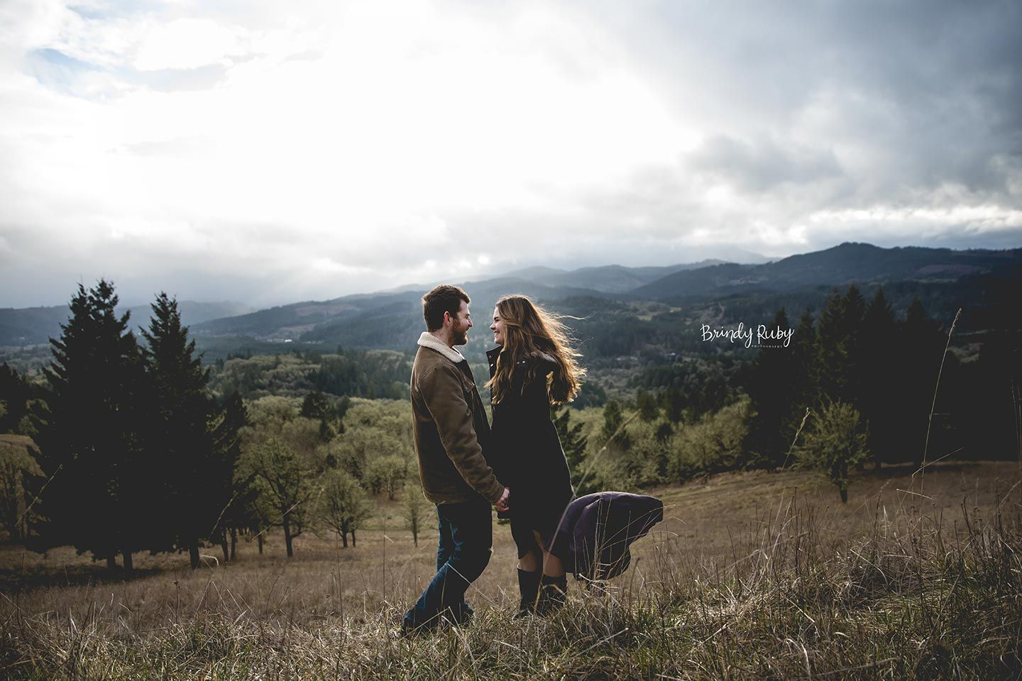 couple facing each other and holding hands on a grassy hill with mountains and clouds in the background