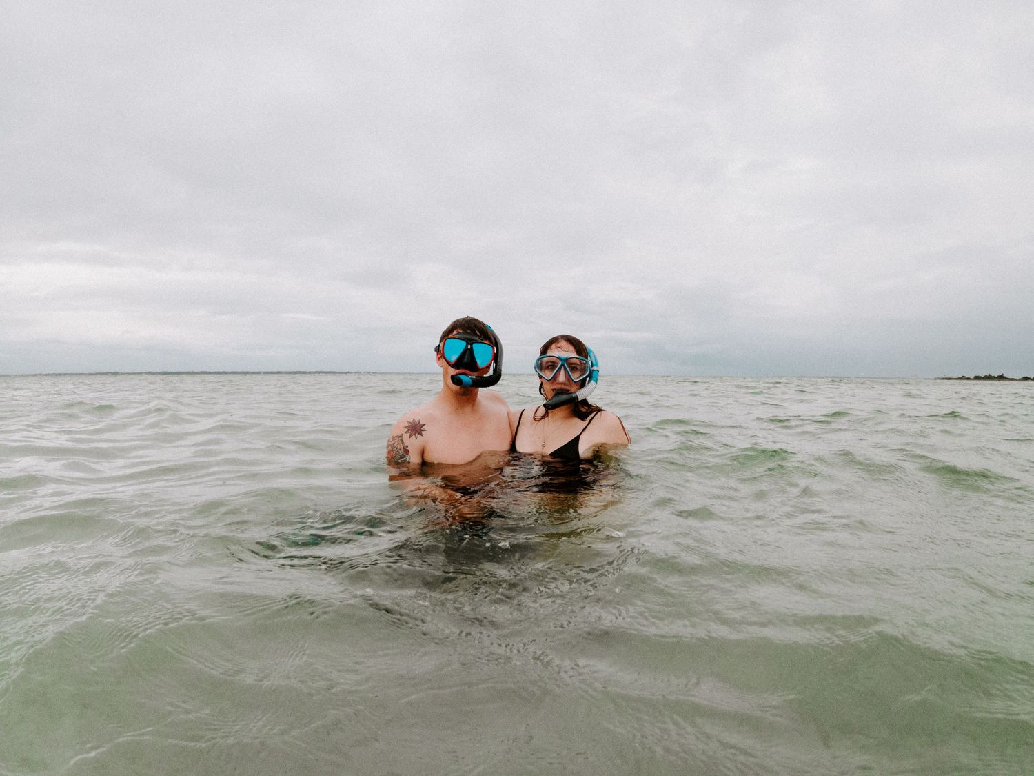 couple looking at the camera with their snorkeling gear on