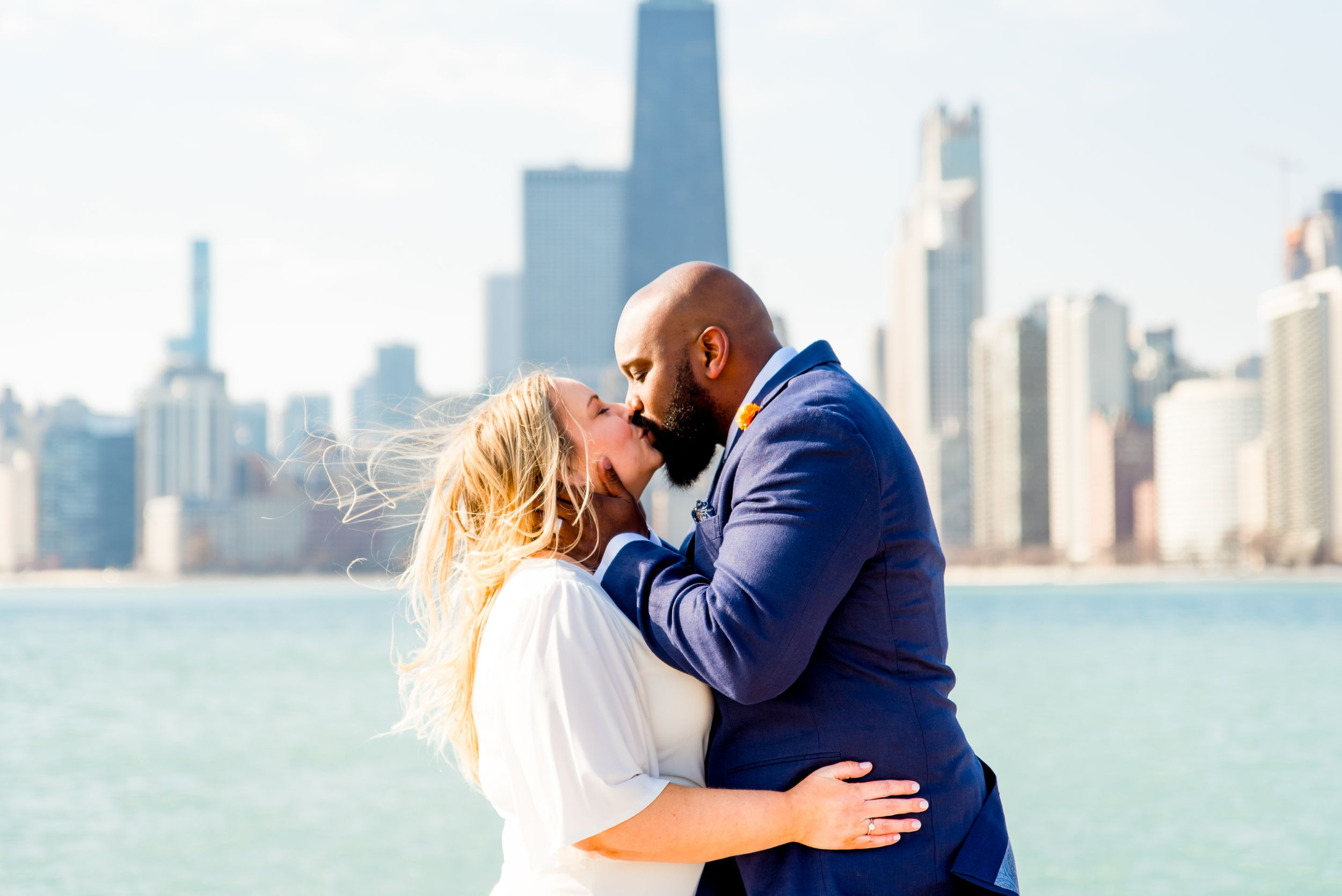 blonde woman and man with beard in navy suit kissing on pier at north avenue beach after chicago elopement