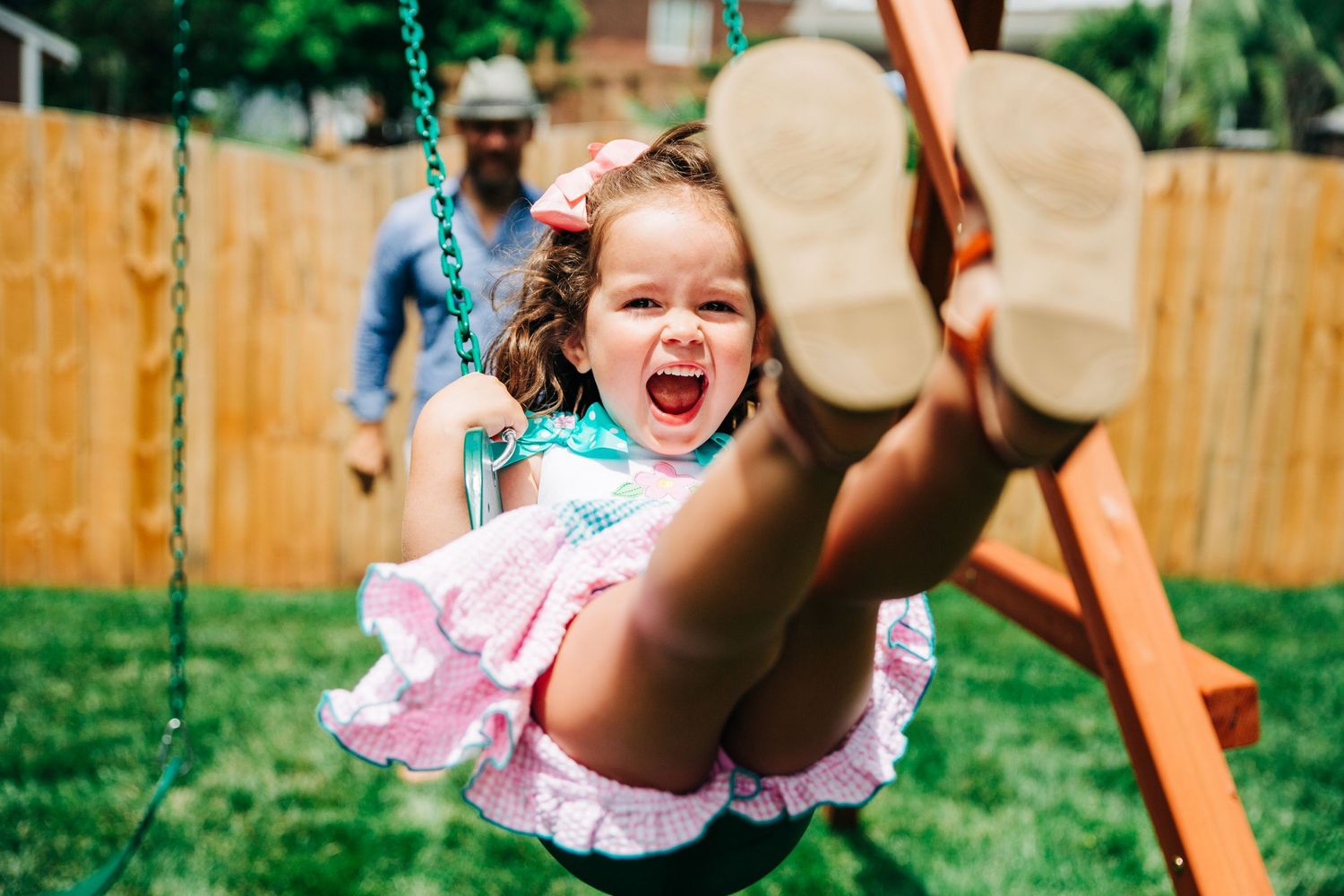 Young girl swinging on swing during her fun family photos