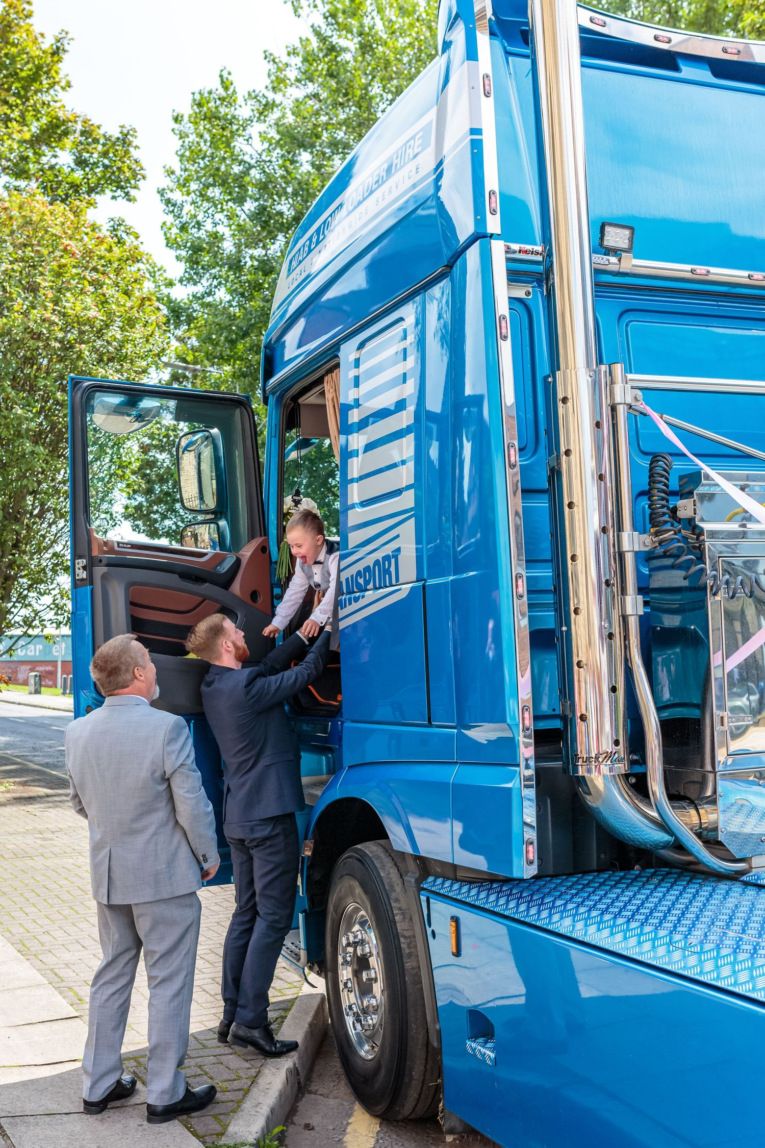 groom lifts his son down from the cab of the hgv wedding transport