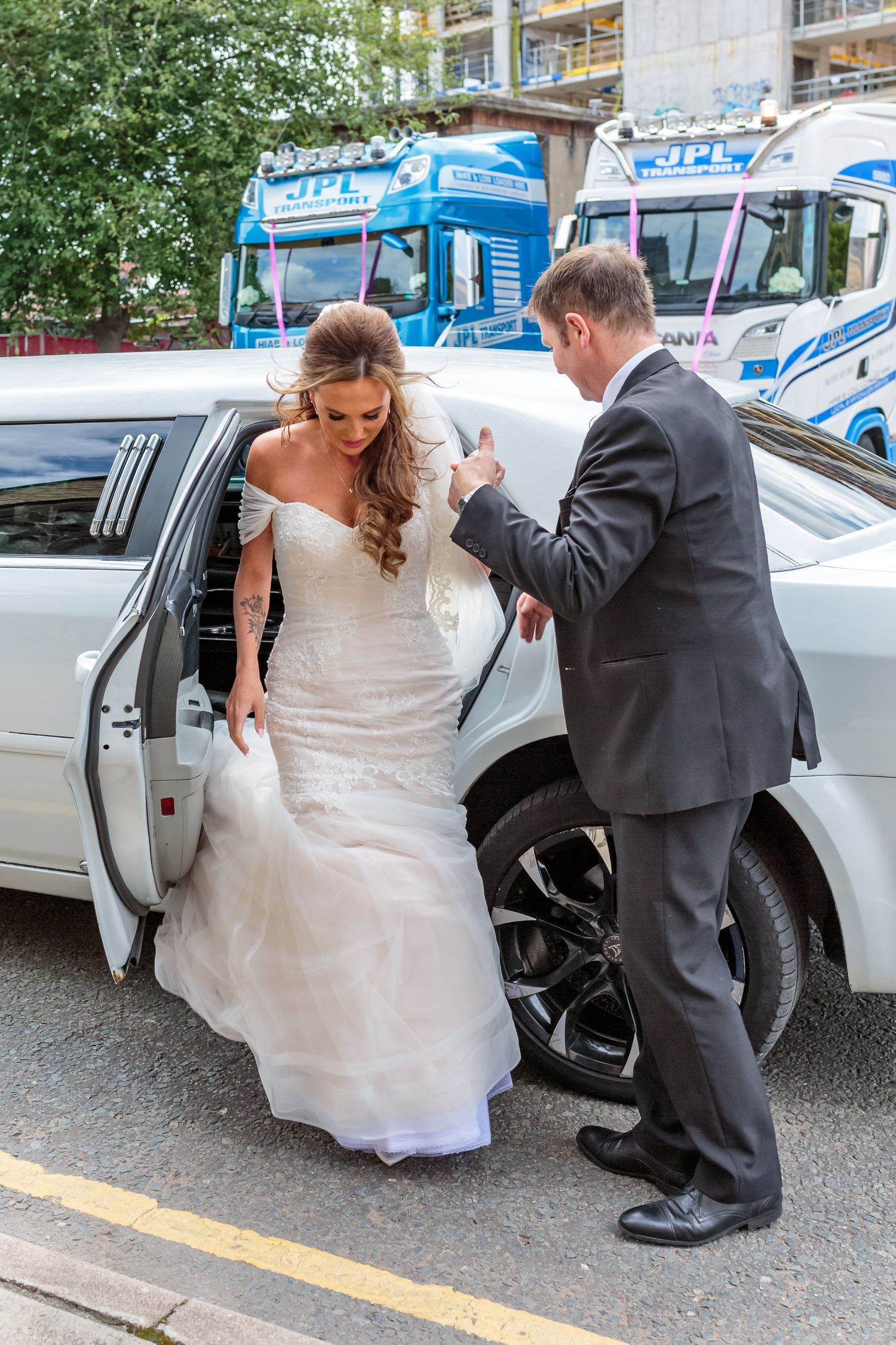 bride helped out of the stretch limo by the chauffeur