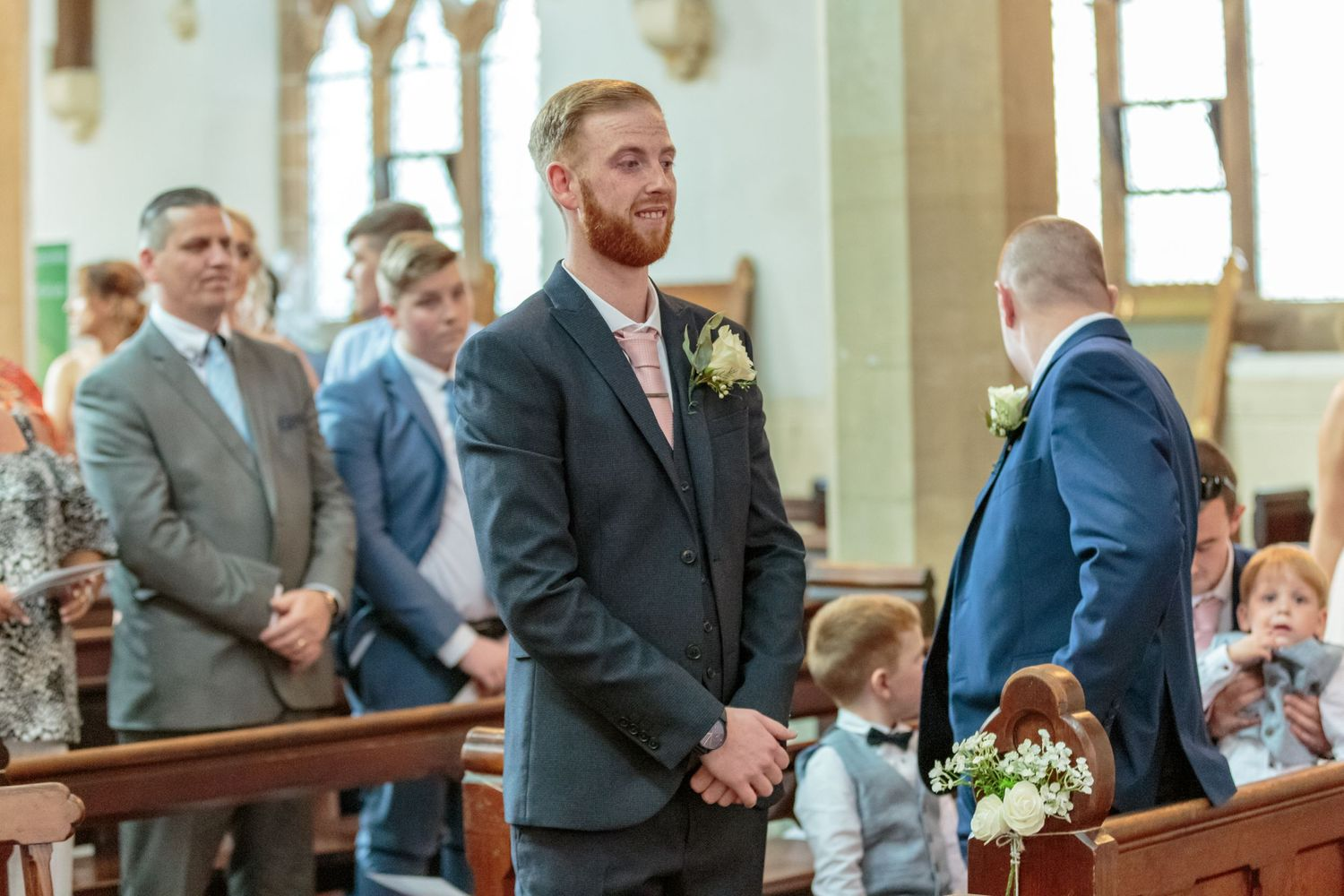 groom keeps his eyes to the front as he waits in church for the bride his hands clasped tightly in front of him