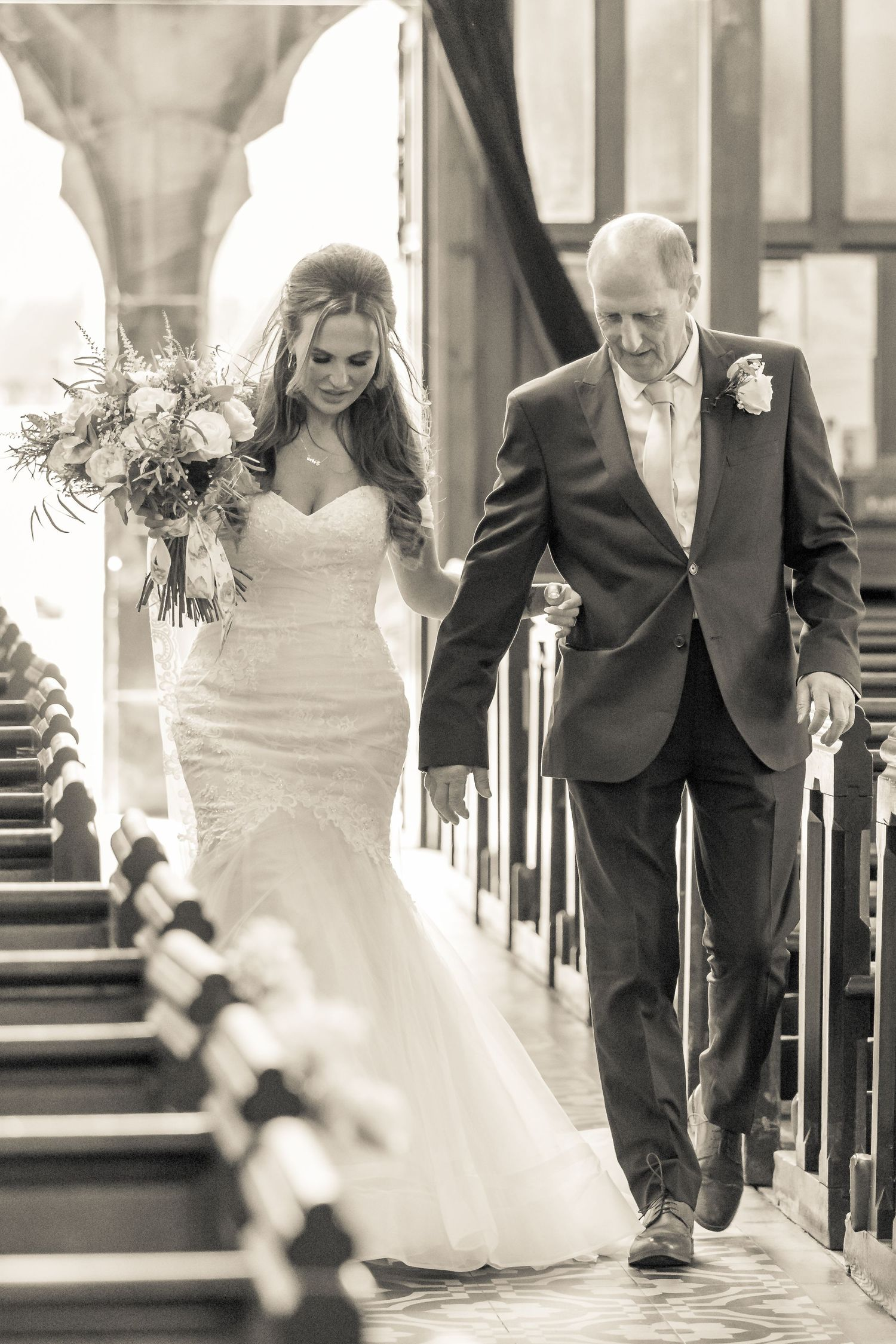 stunning bride carrying her bouquet escorted down the aisle by her father