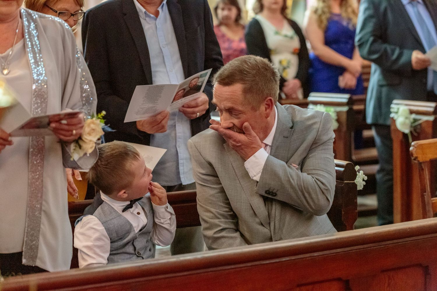 wedding guests keeps the couples young son entertained in church putting their hands over their mouths