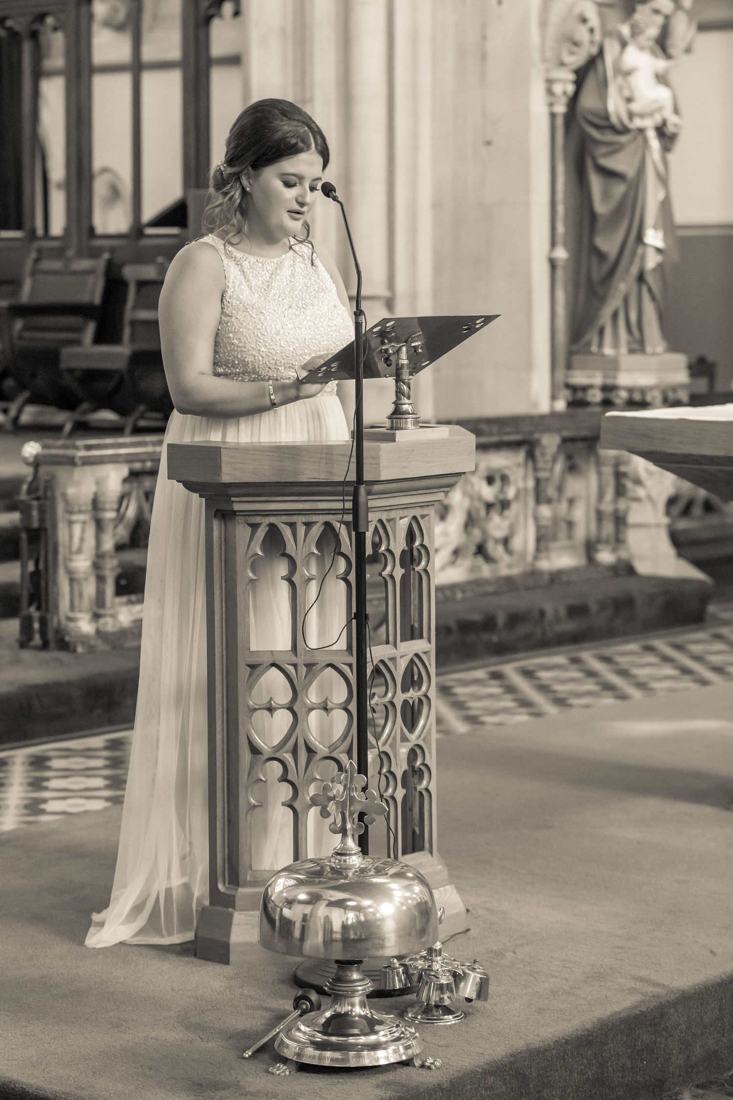bridesmaid stands up at the front of the church to give a reading