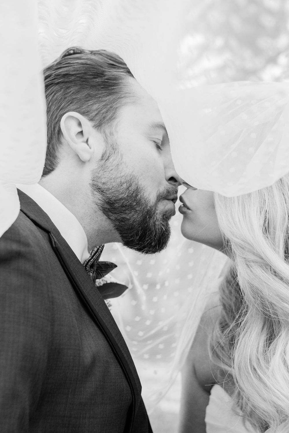 Black and White bride and groom kissing under veil Melissa and Chad Sandy Springs Wedding