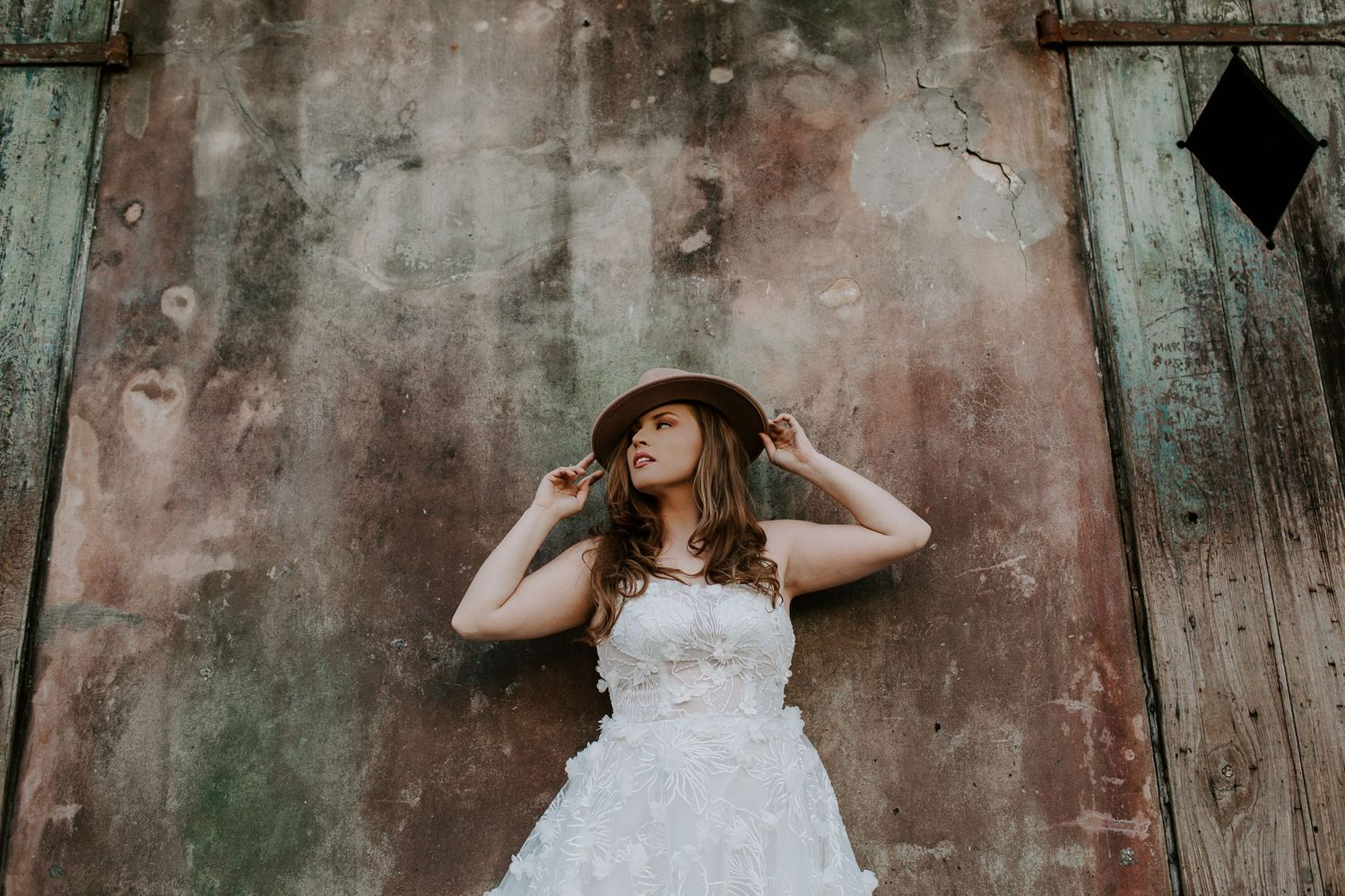 Bride holding her hat leaning up against a wall in the French Quarter during her urban New Orleans elopement