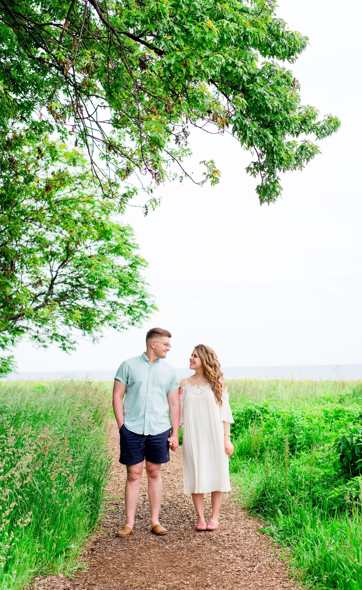 engaged couple in white dress and blue shirt hold hands and look at each other under a big green tree in the summer