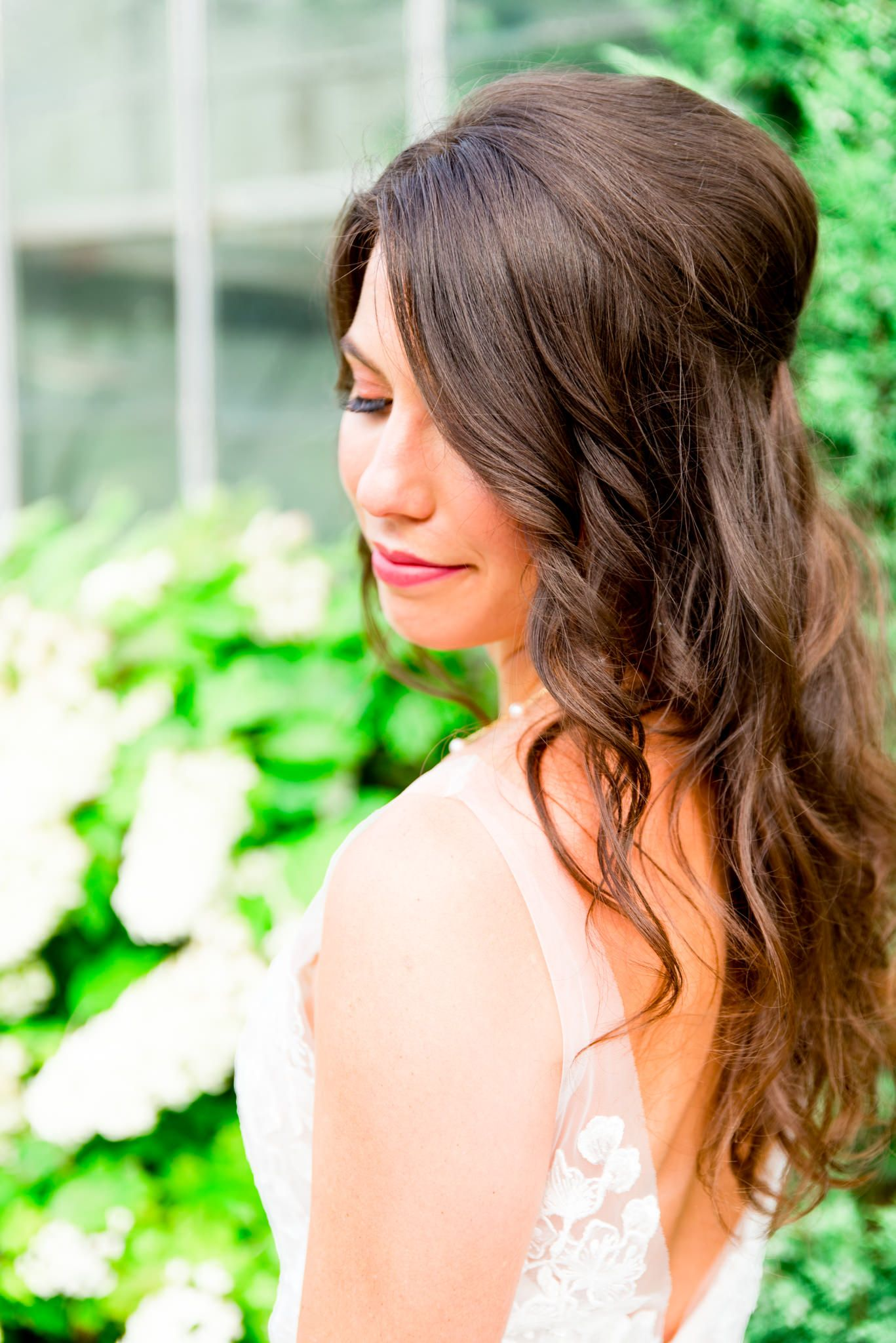 bride with brown hair in loose curls smiling over her shoulder in front of white hydrangea bush at conservatory wedding