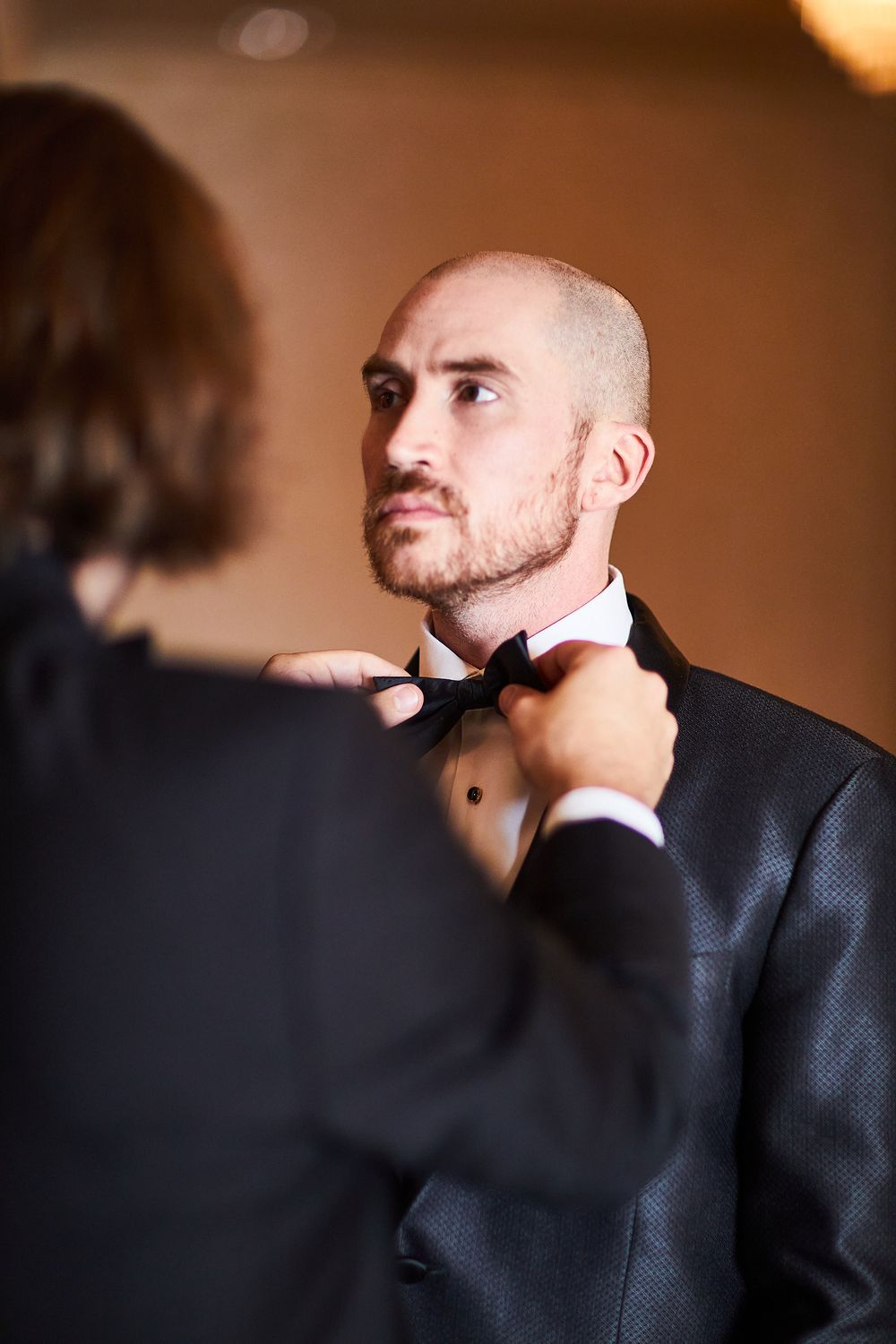 A groomsman adjusting Joe's bowtie as they prepare for the ceremony in the Seelbach Hotel in Louisville, KY.