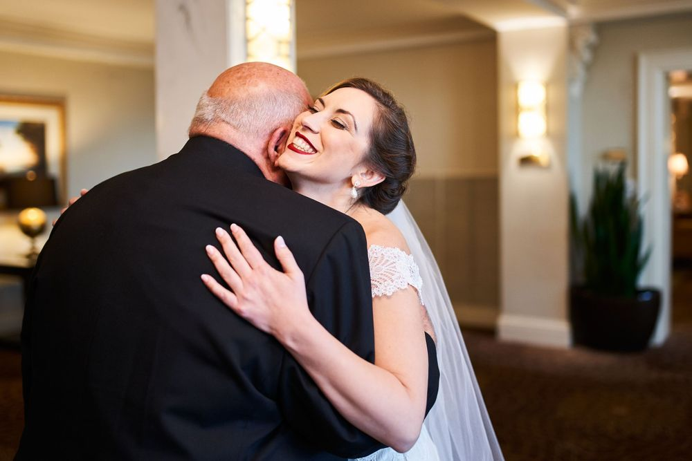 Gabby sharing a hug with her father as he sees her for a first look before the ceremony in the Seelbach Hotel.