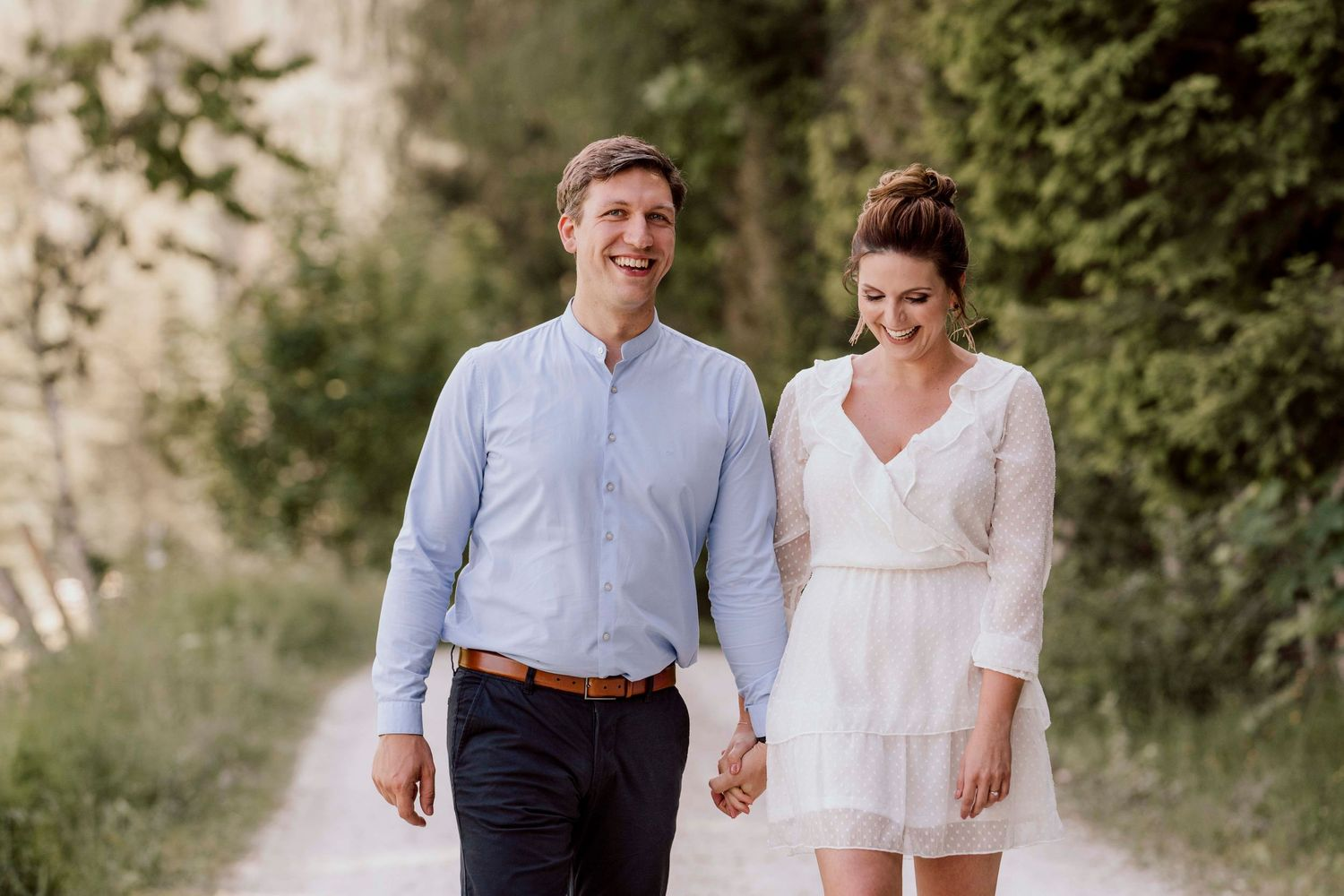 romantic couple walking on a path along a forest looking and smiling