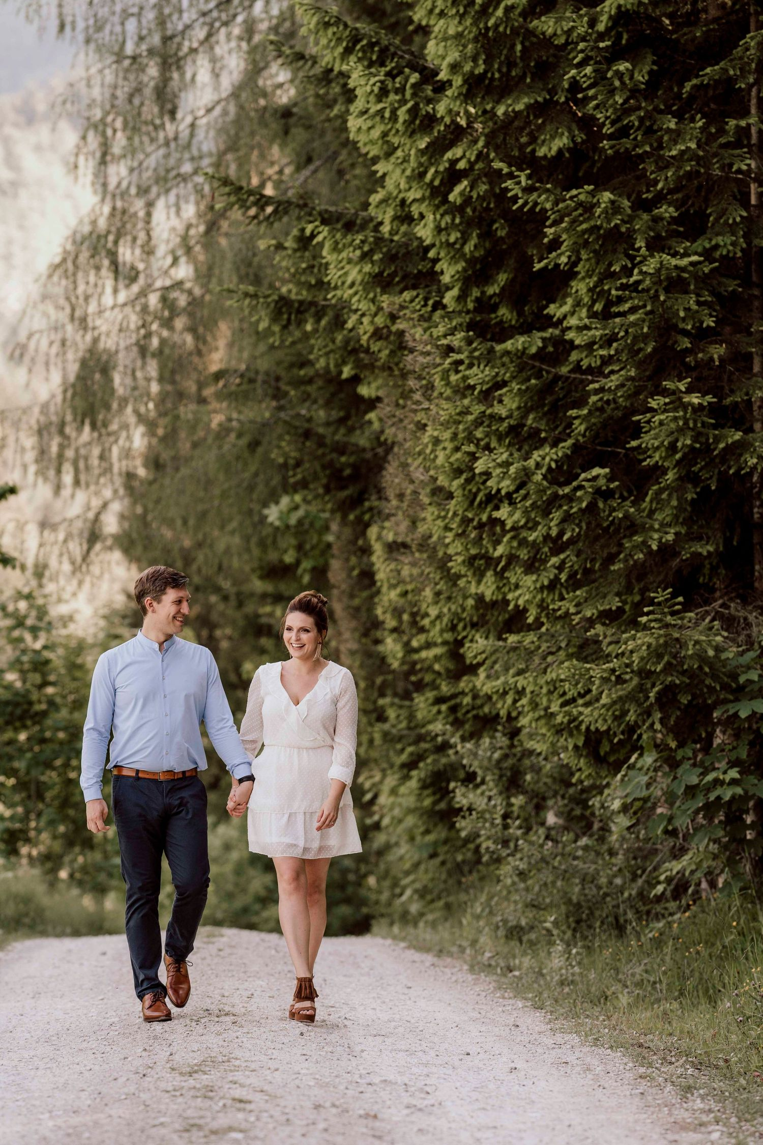 romantic couple walking on a path along a forest