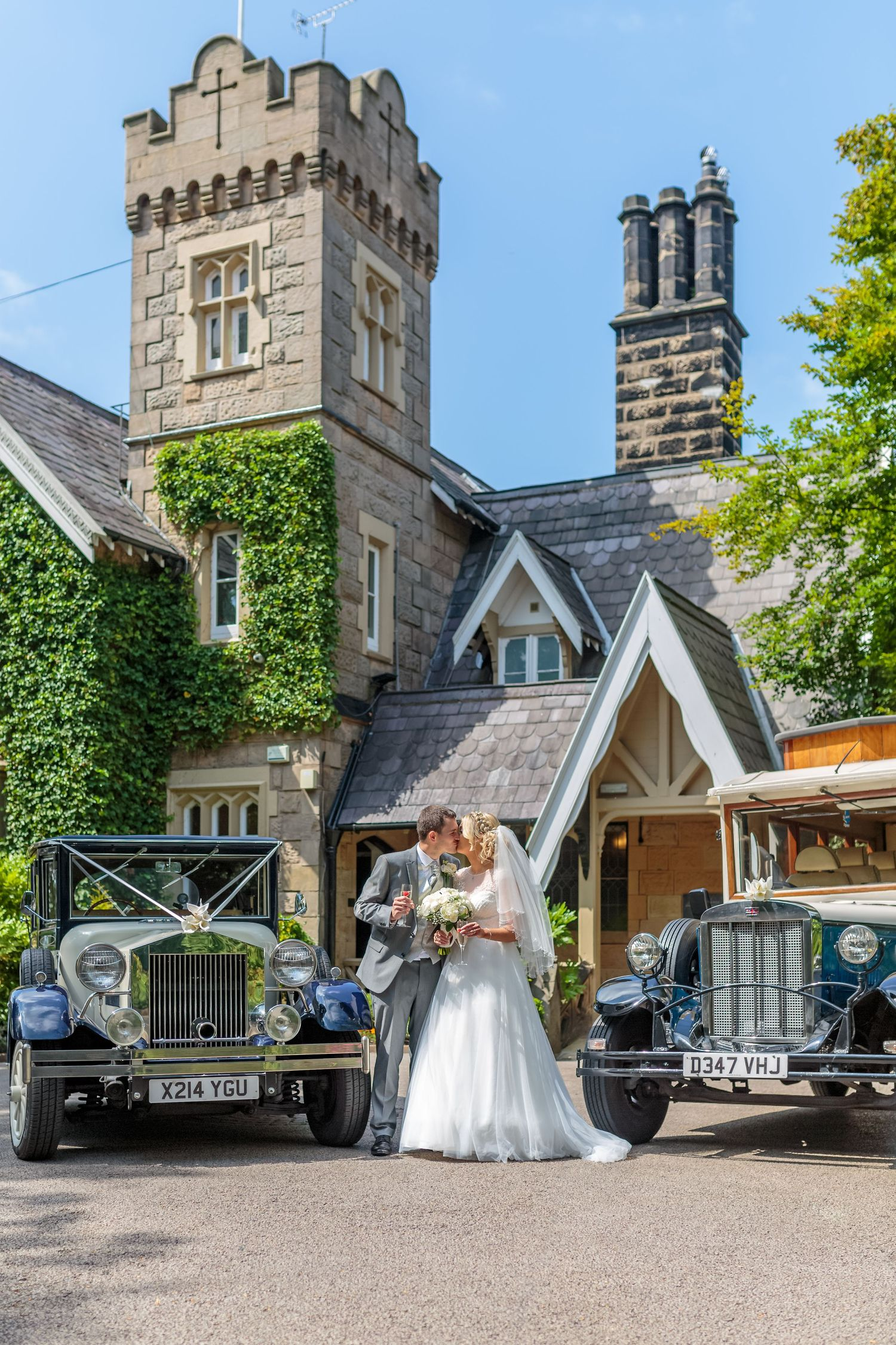 bride and groom pose kissing alongside the wedding cars at the front of west tower exclusive wedding venue