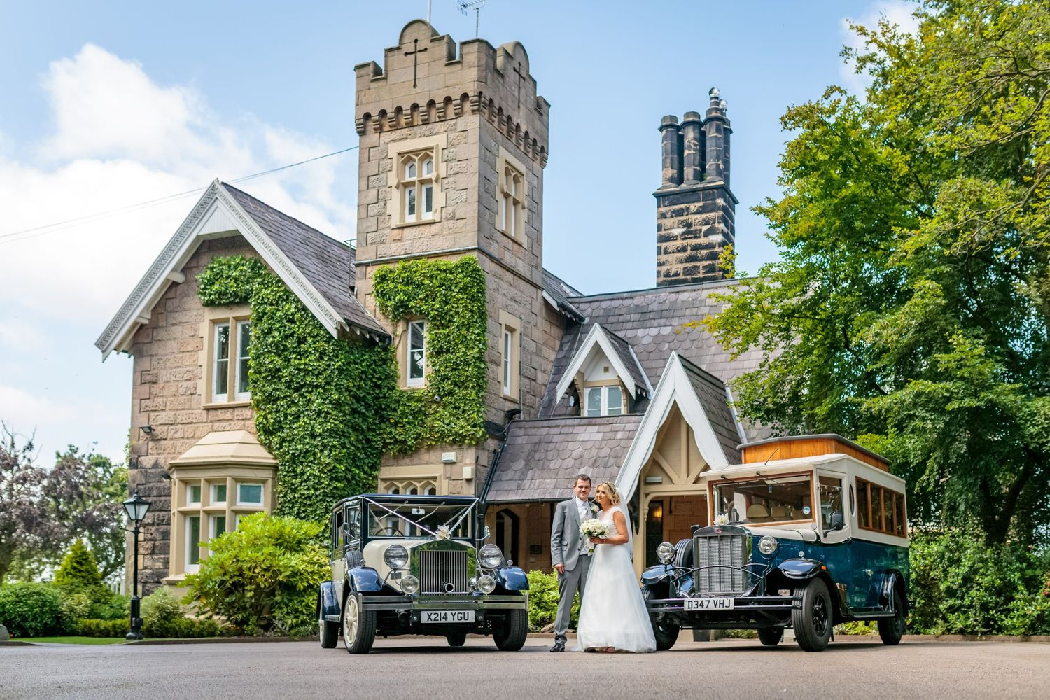 wide shot of the bride and groom posing with the wedding cars outside the front of west tower ormskirk