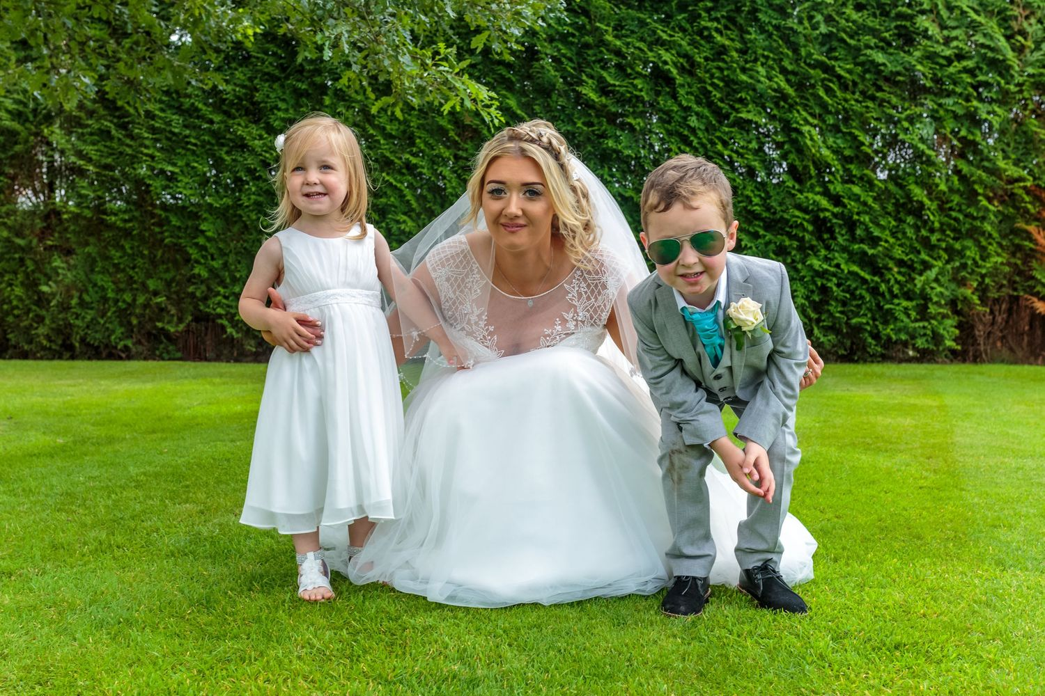 bride crouches down for a photograph with the little flower girl and the page boy wearing mirrored sunglasses