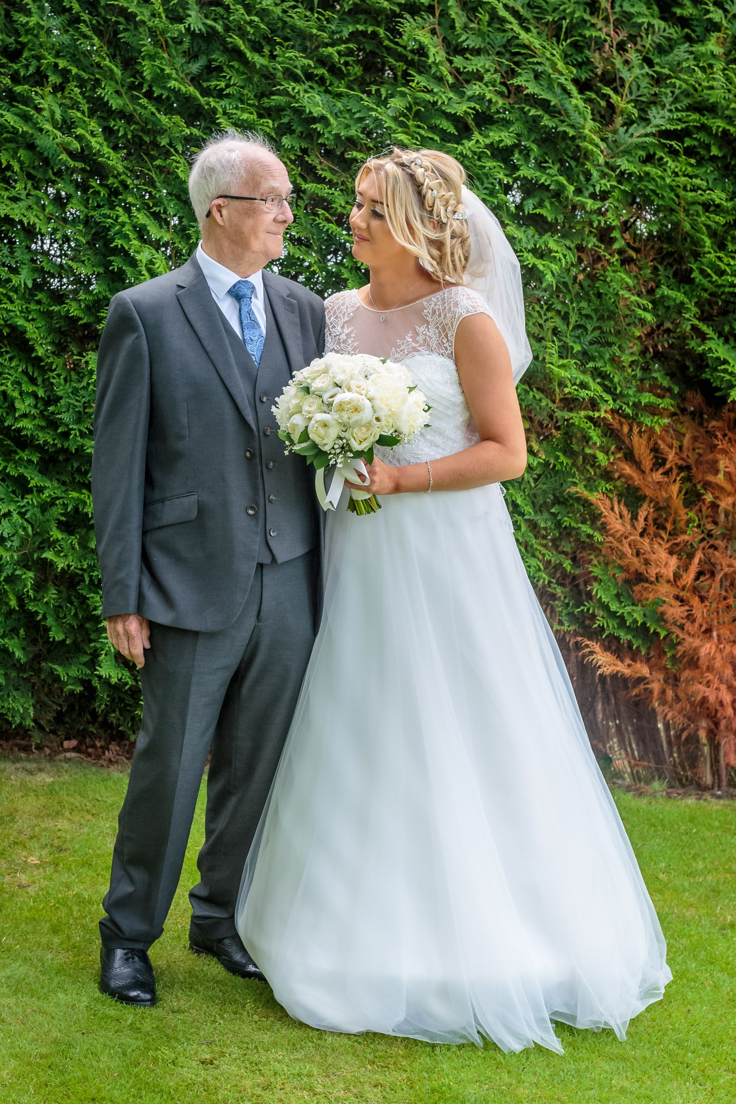 bride and her grandfather stand smiling at each other in the gardens at west tower