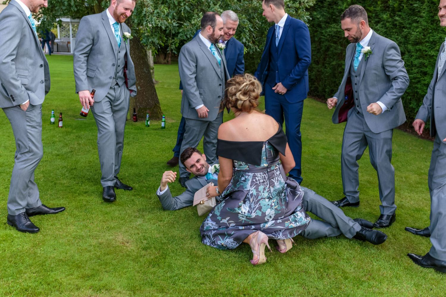 best man lying on the floor surrounded by the groomsmen with a lady kneeling over him