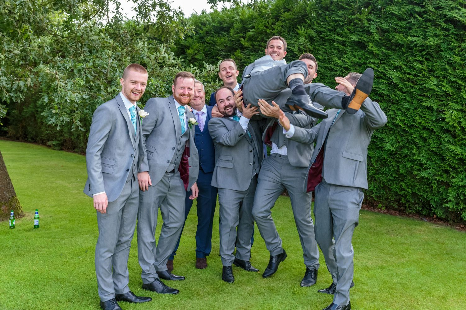 groomsmen lift the groom in the air in the garden at west tower wedding venue