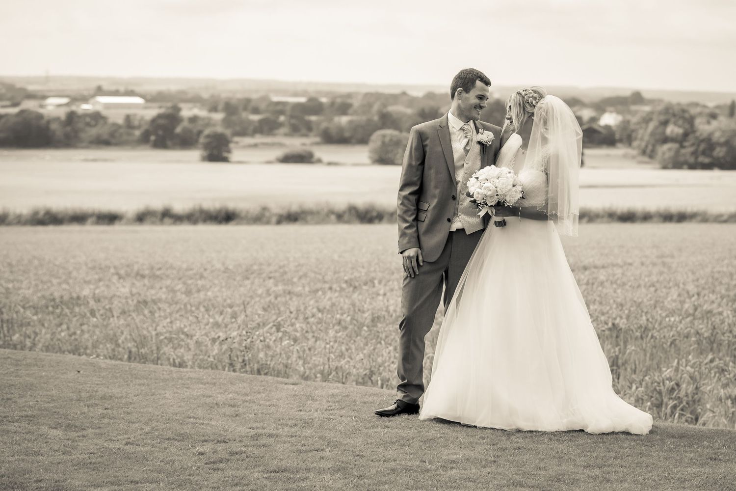bride and groom smiling looking at each other in the gardens at west tower countryside in the background
