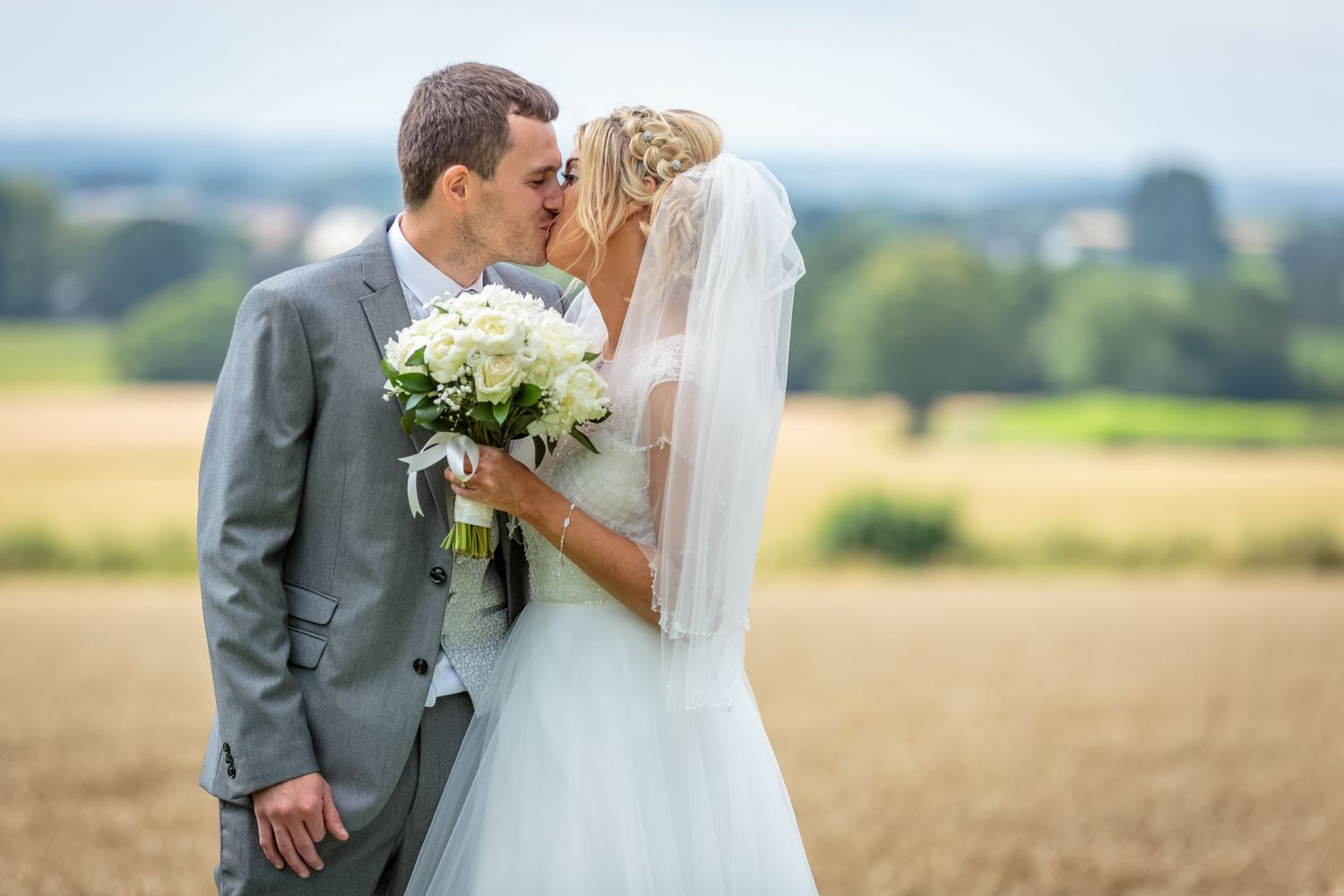 bride holding her bouquet kisses the groom with the countryside as a backdrop